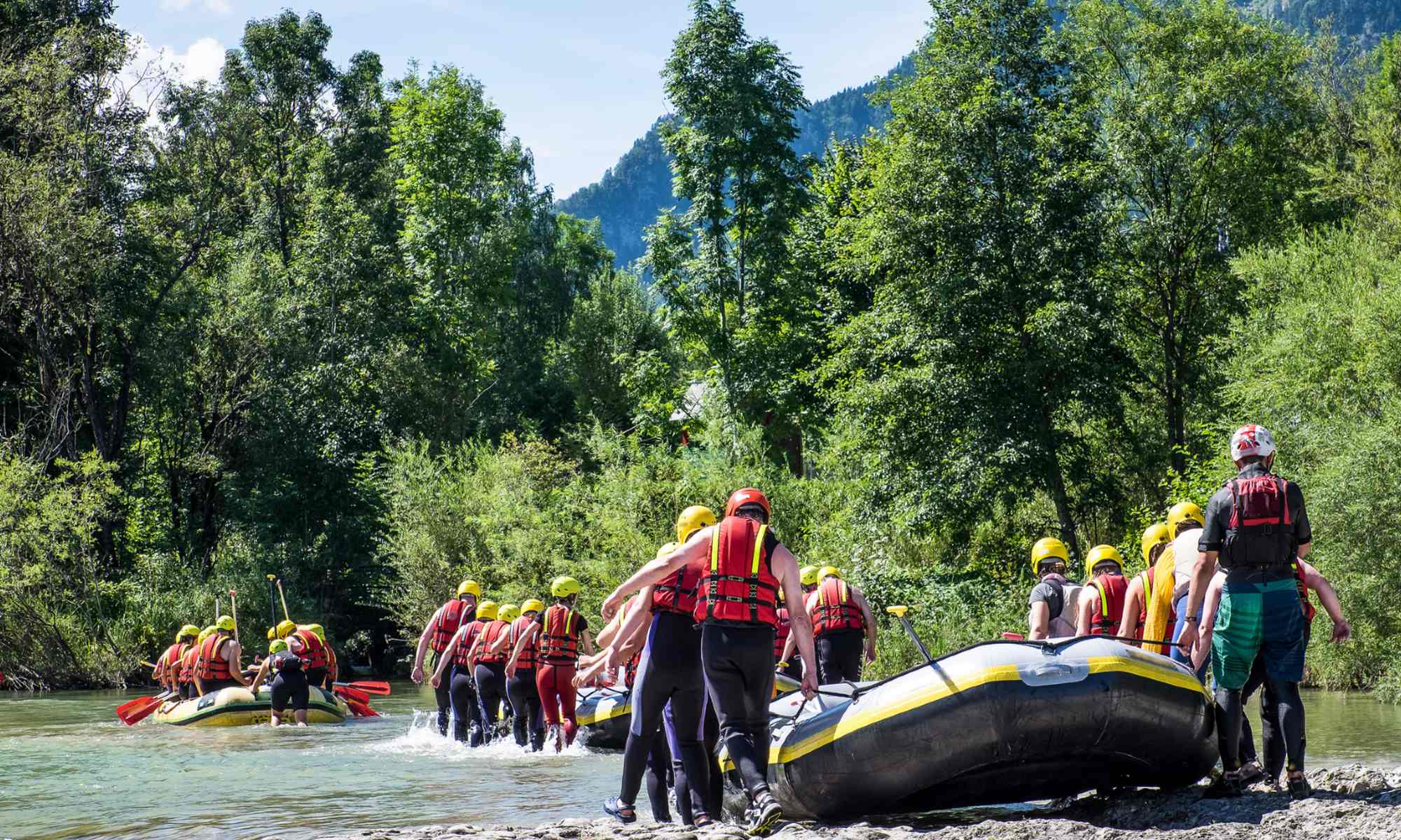 Several groups of people carrying their rafts towards the entry point of the river.