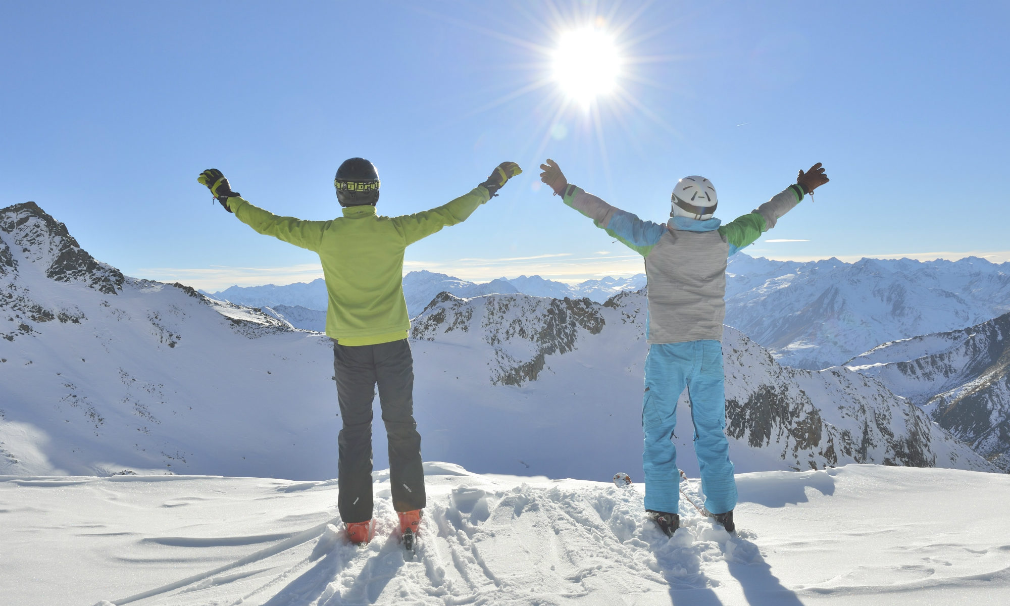 Two skiers view the snowy landscape around them from a sunny peak.