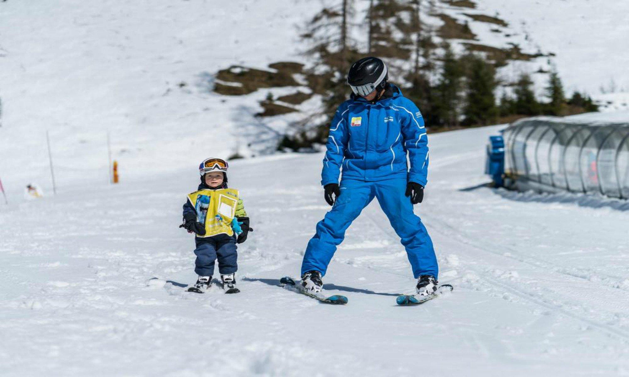 Een jonge skiër en zijn skileraar tijdens een skiles in Flachau.