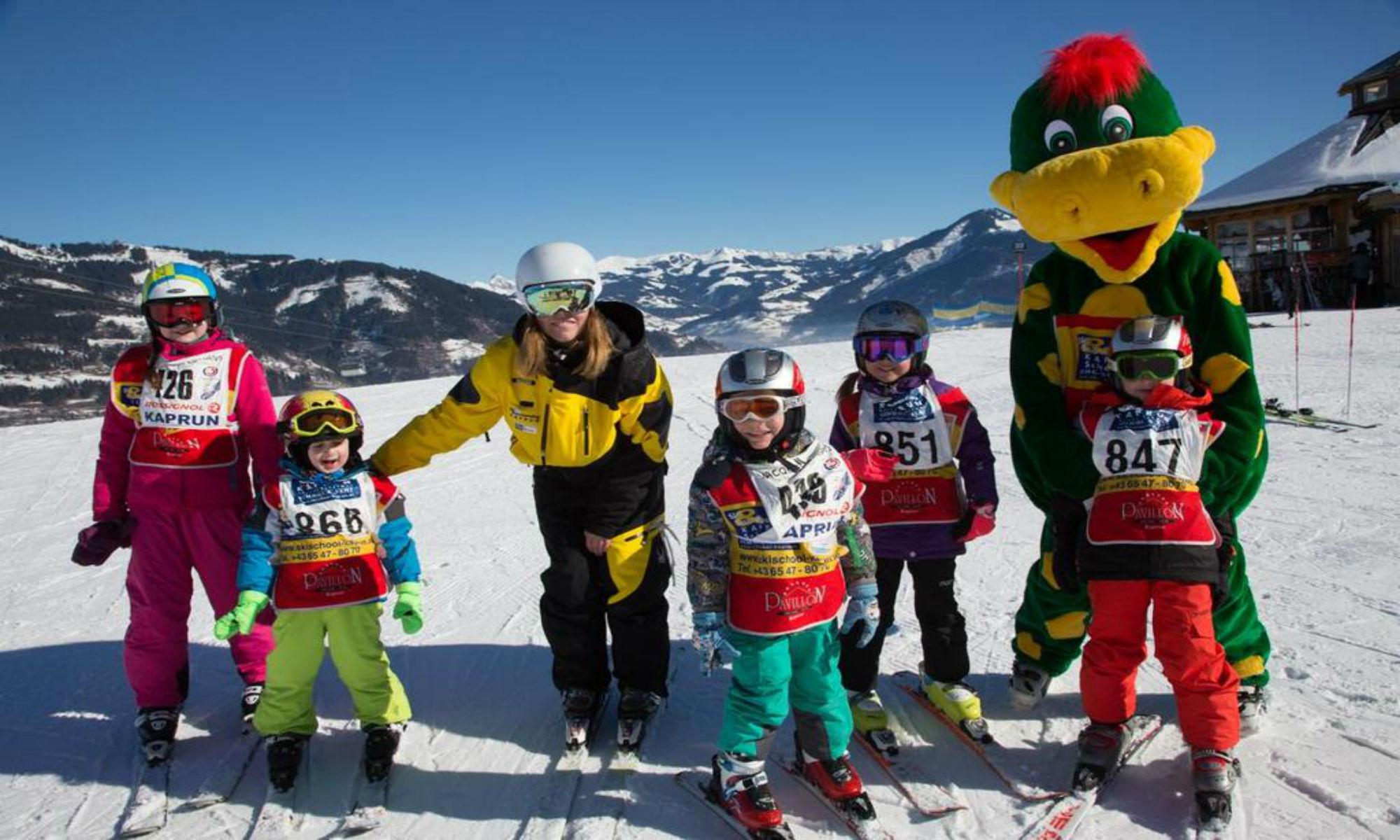 Een groepje kinderen poseert tijdens hun skiles met hun skilerares en Dino de Dinosaurus, de mascotte van het kinderland.