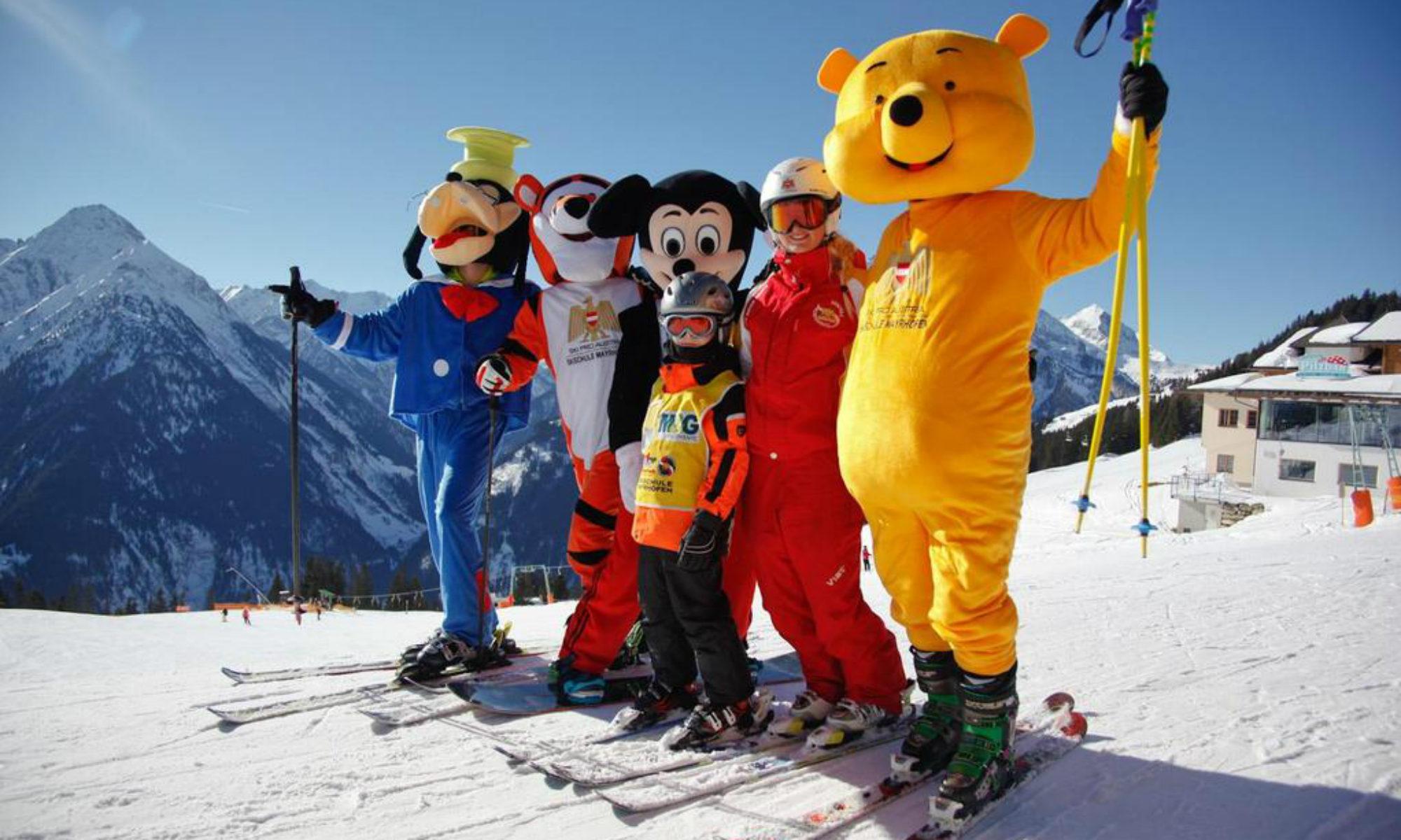 De mascottes van de skischolen van Mayrhofen, waaronder Mickey Mouse, poseren samen met een skileraar en een leerling.