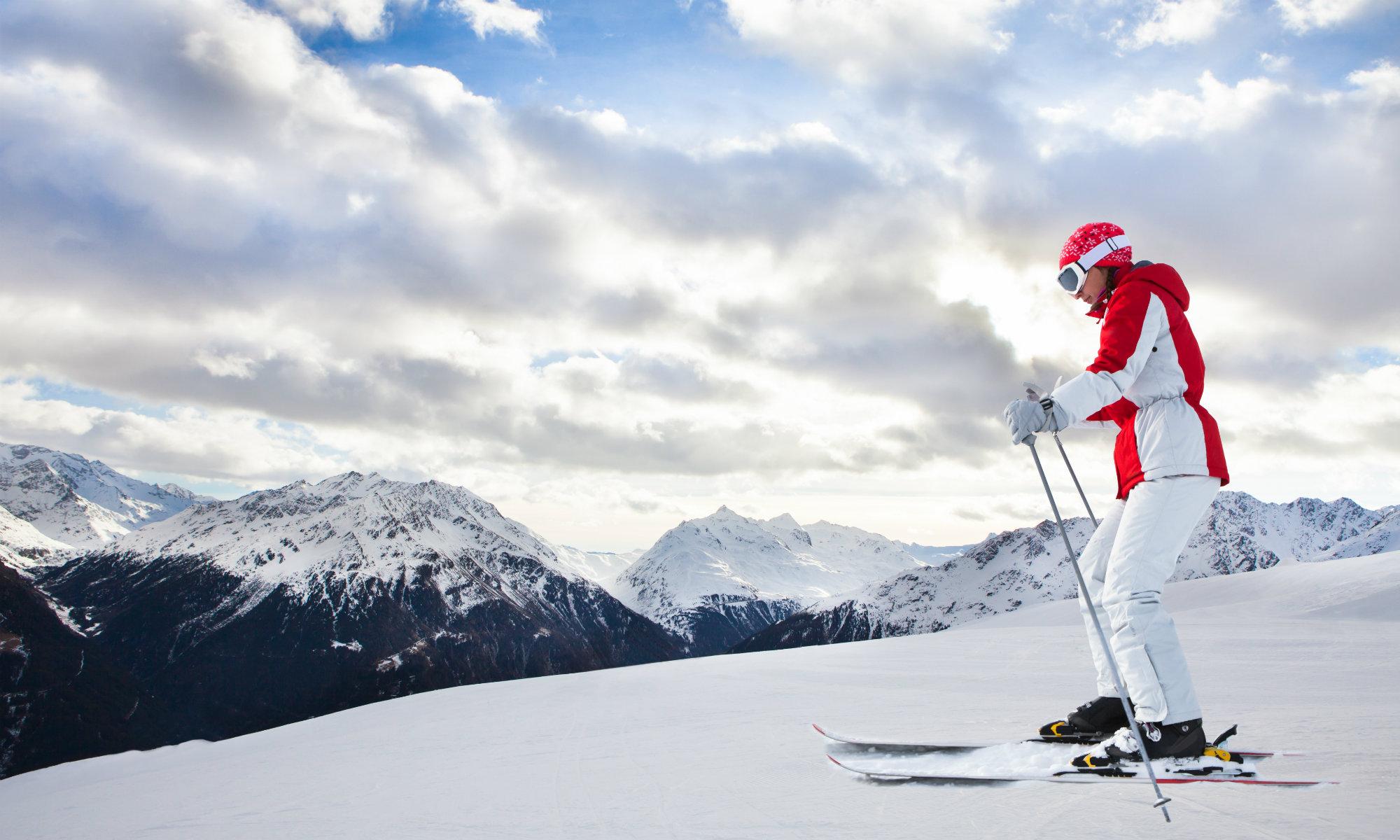 Due sciatori fanno degli esercizi di riscaldamento sulla cima della montagna.