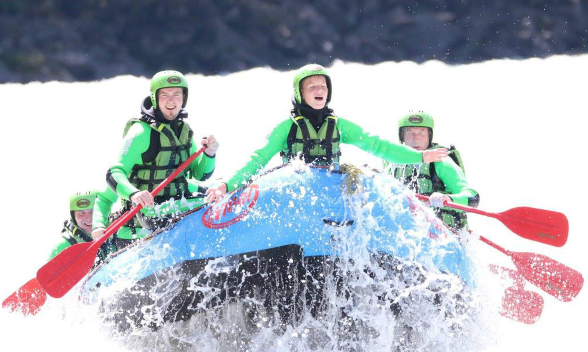 A family in a rubber dinghy rafting along the white waters of the Inn River in Tyrol.