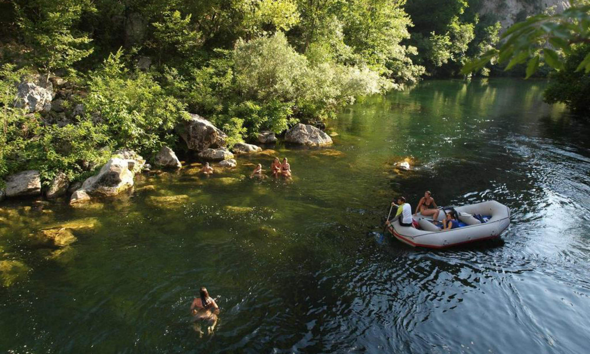 A group of people cooling off in the water during a white water rafting tour on the Cetina River.