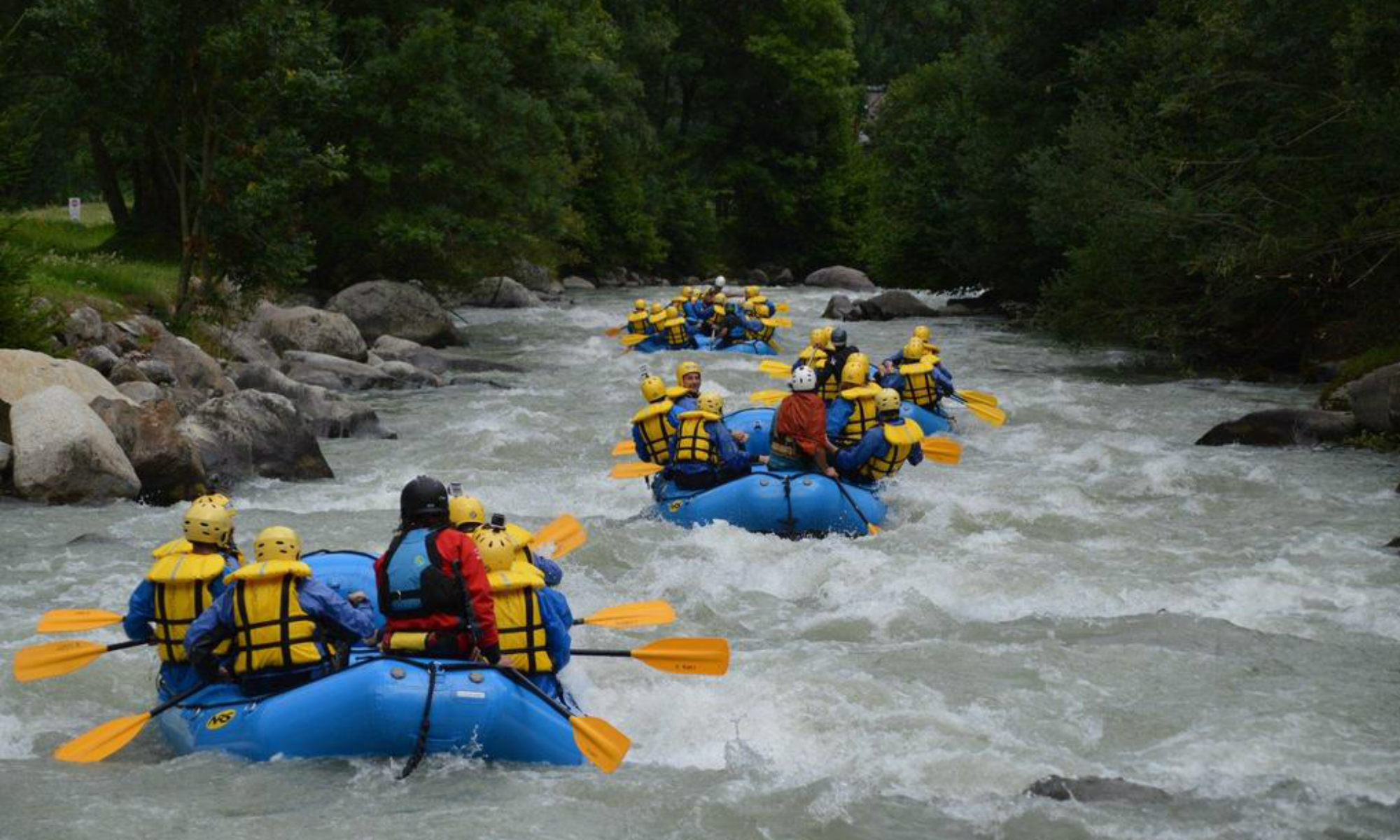 Several groups of people rafting on the Noce River in Val di Sole.
