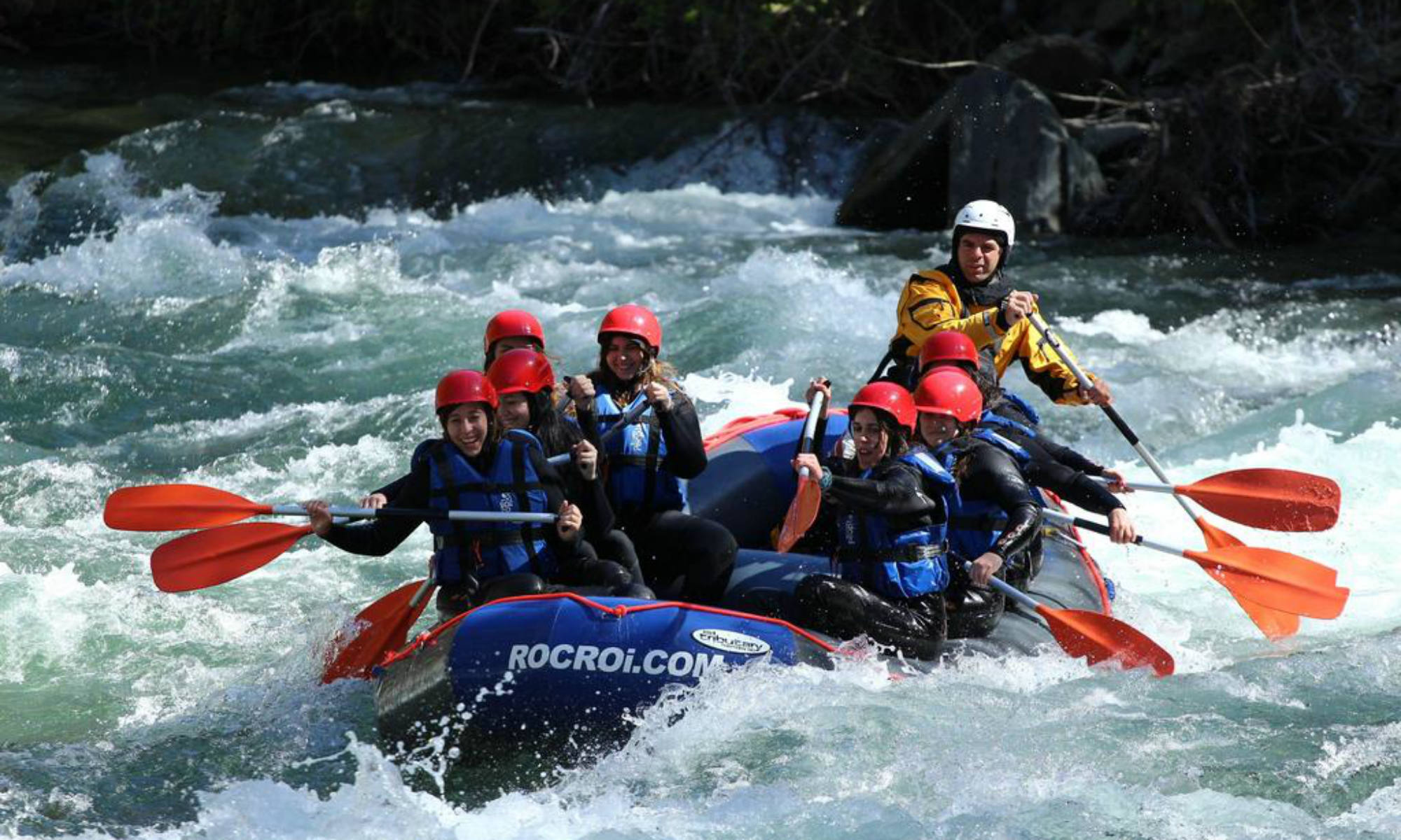 A group of people navigating their dinghy along the rousing Noguera River.