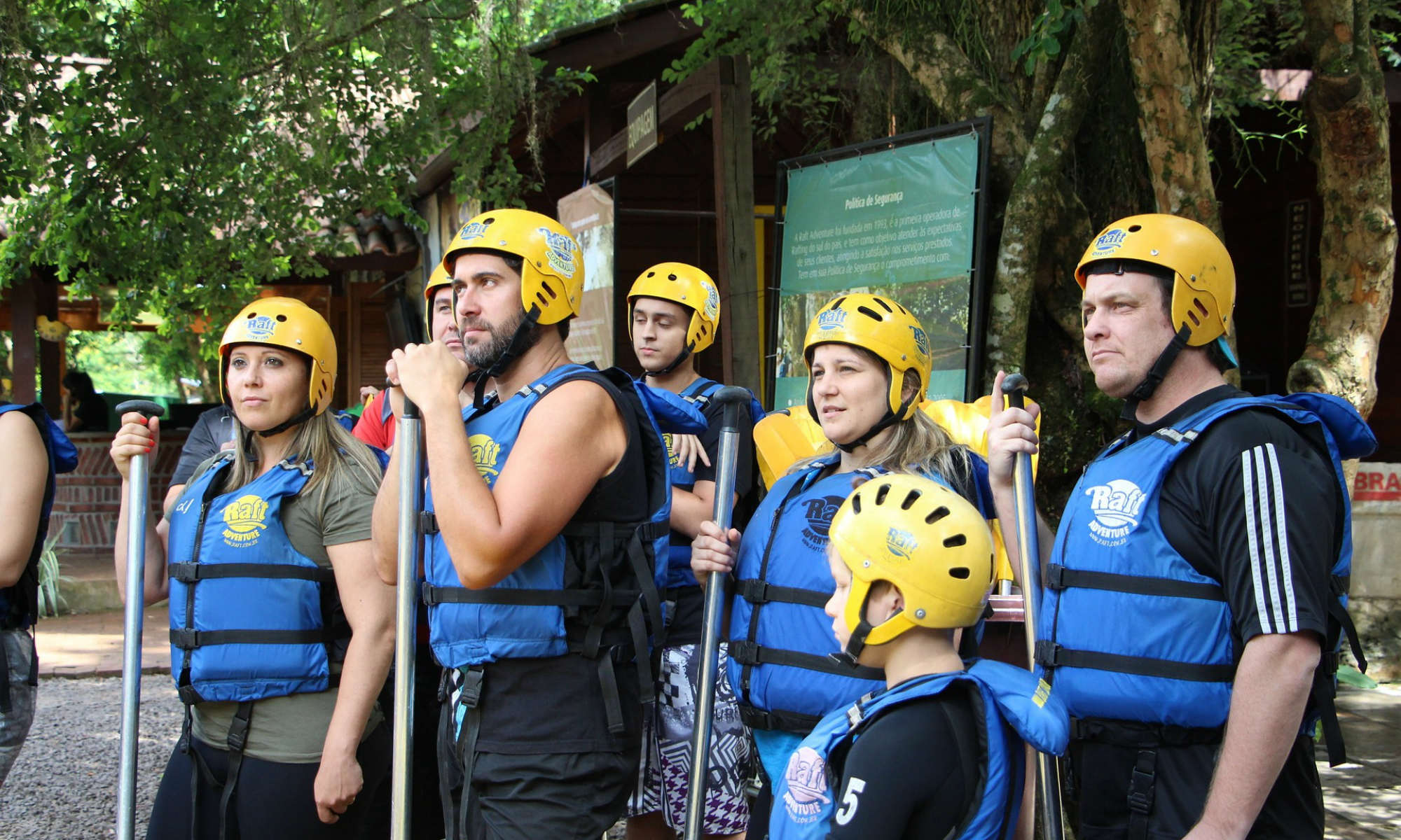 A family is listening to the safety instructions before embarking on their white water rafting tour.