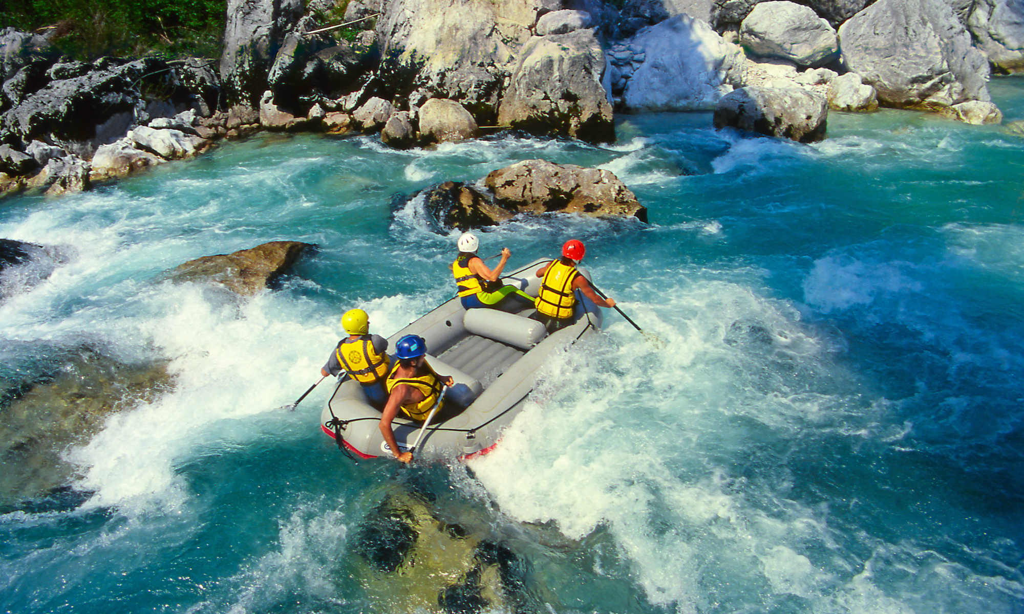 A group of people in a raft is navigating through a rocky passage on an emerald green river.