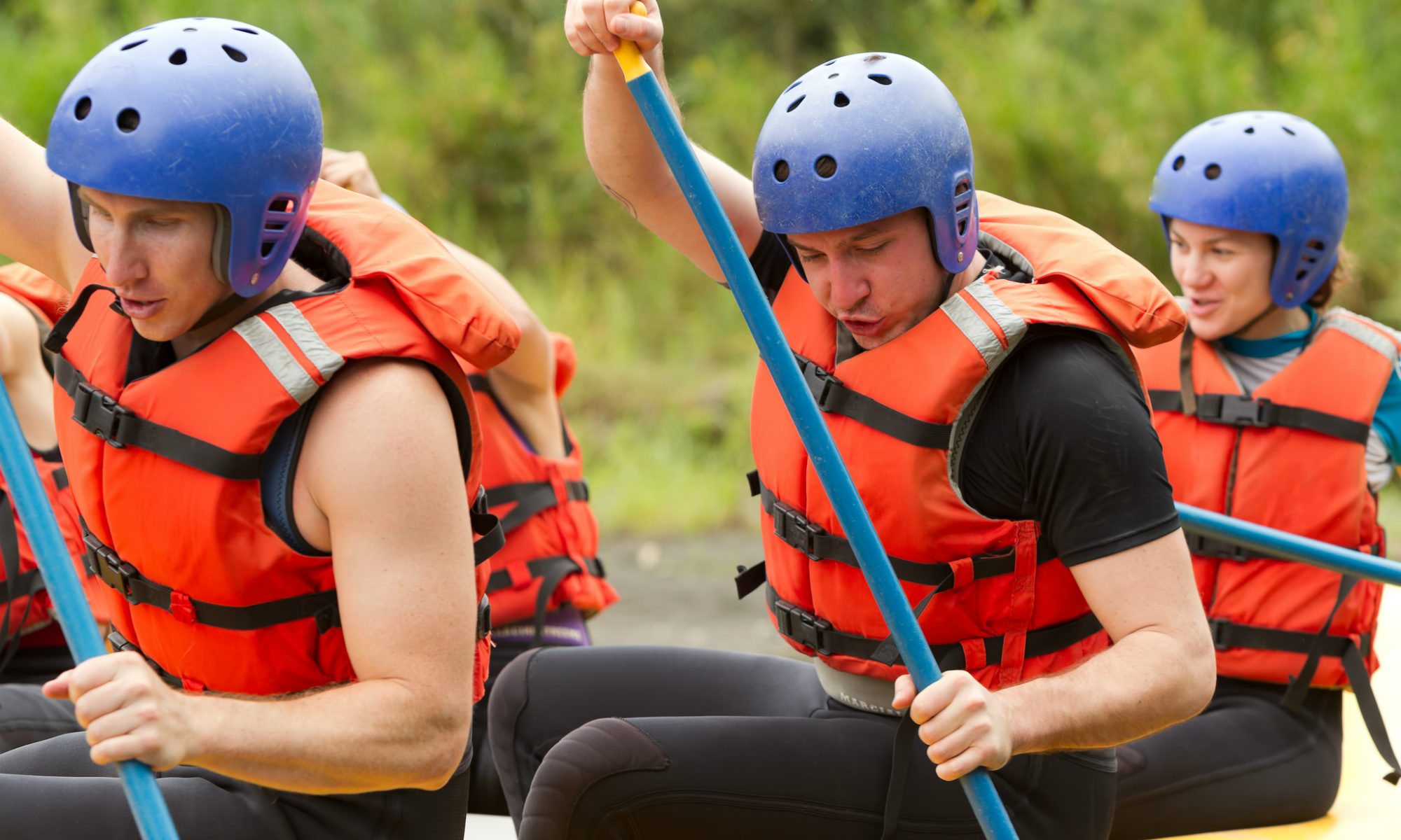 A group of white water rafting participants using their paddles to steer the boat.