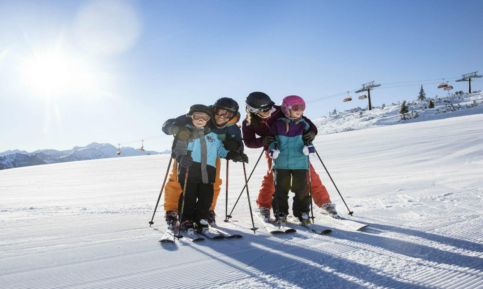Een gezin poseert voor een foto terwijl ze leren skiën in Oostenrijk.
