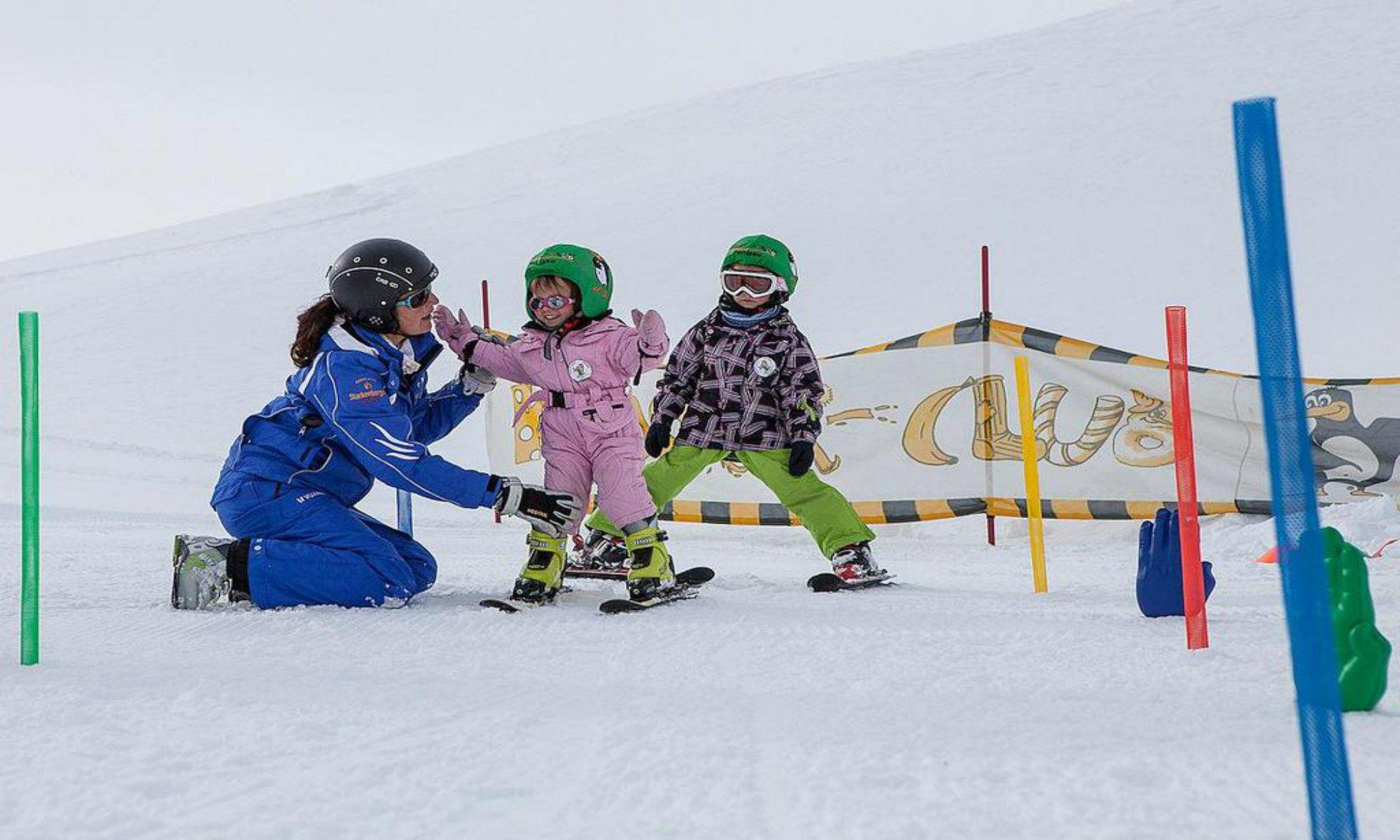 Een skilerares leert kinderen de juiste skitechniek tijdens een skiles in het skigebied van Lermoos.