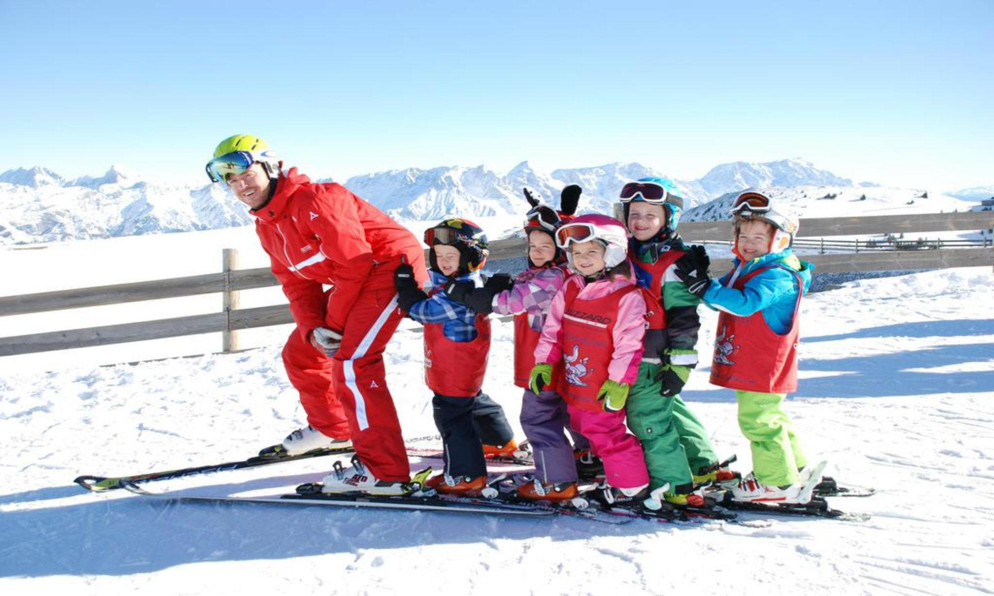 Een groepje kinderen poseert voor een een foto met hun skileraar tijdens hun groepsles in het skigebied van Saalbach-Hinterglemm.