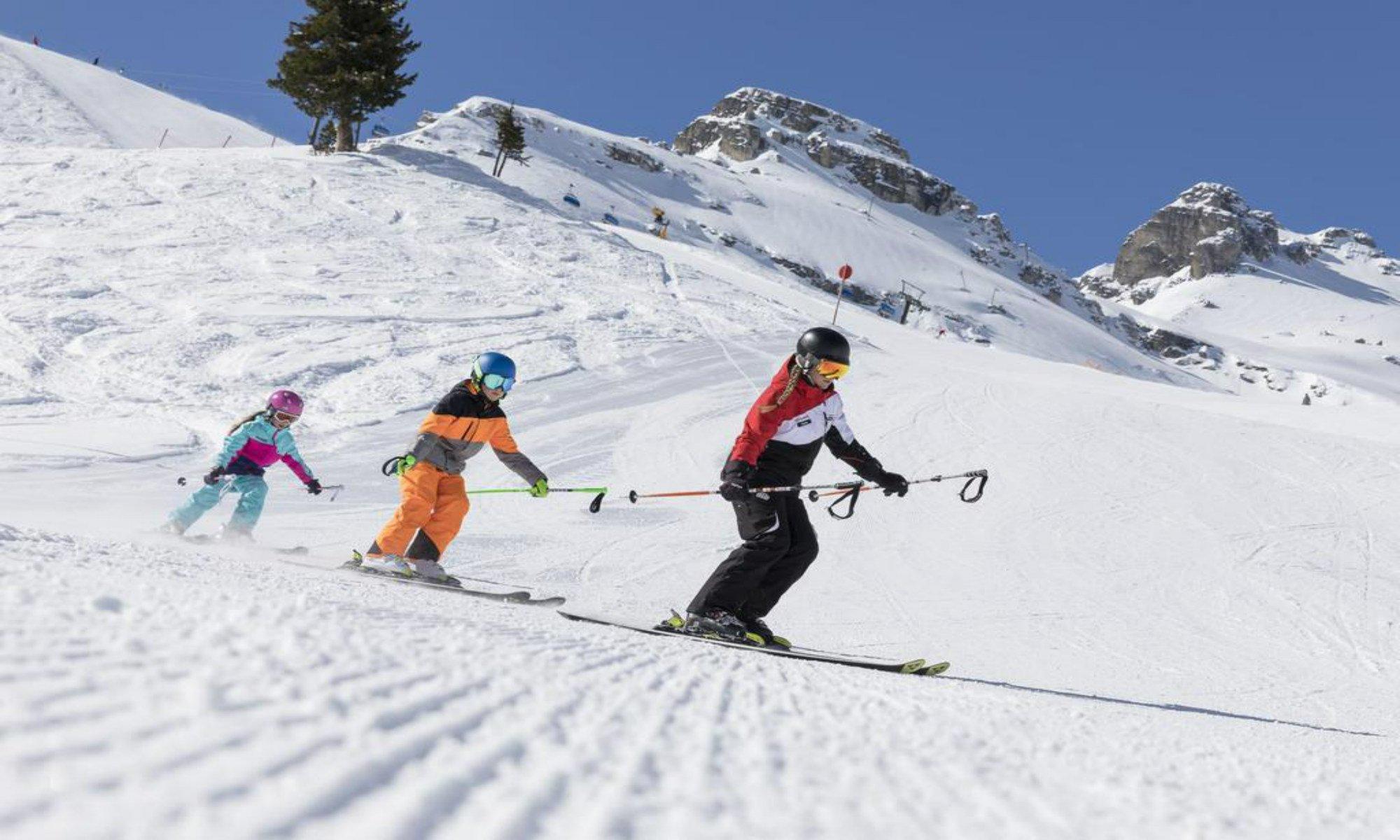 Een skileraar wordt gevolgd door twee jonge leerlingen tijdens een skiles in het skigebied van Schlick-2000-Fulpmes.