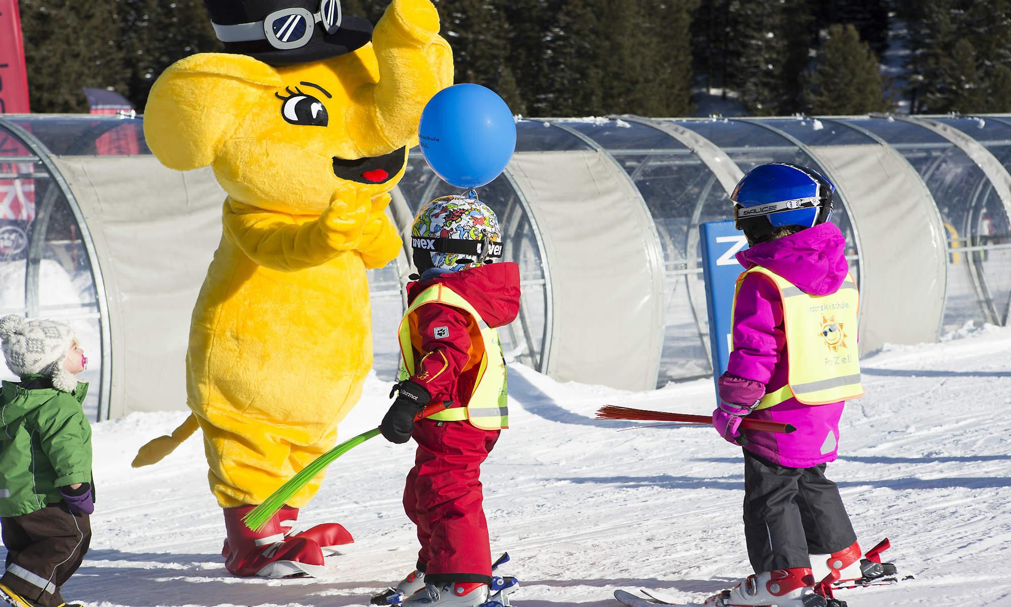 Drie kleine kinderen vermaken zich tijdens de skiles met FUNty, de gele olifant.