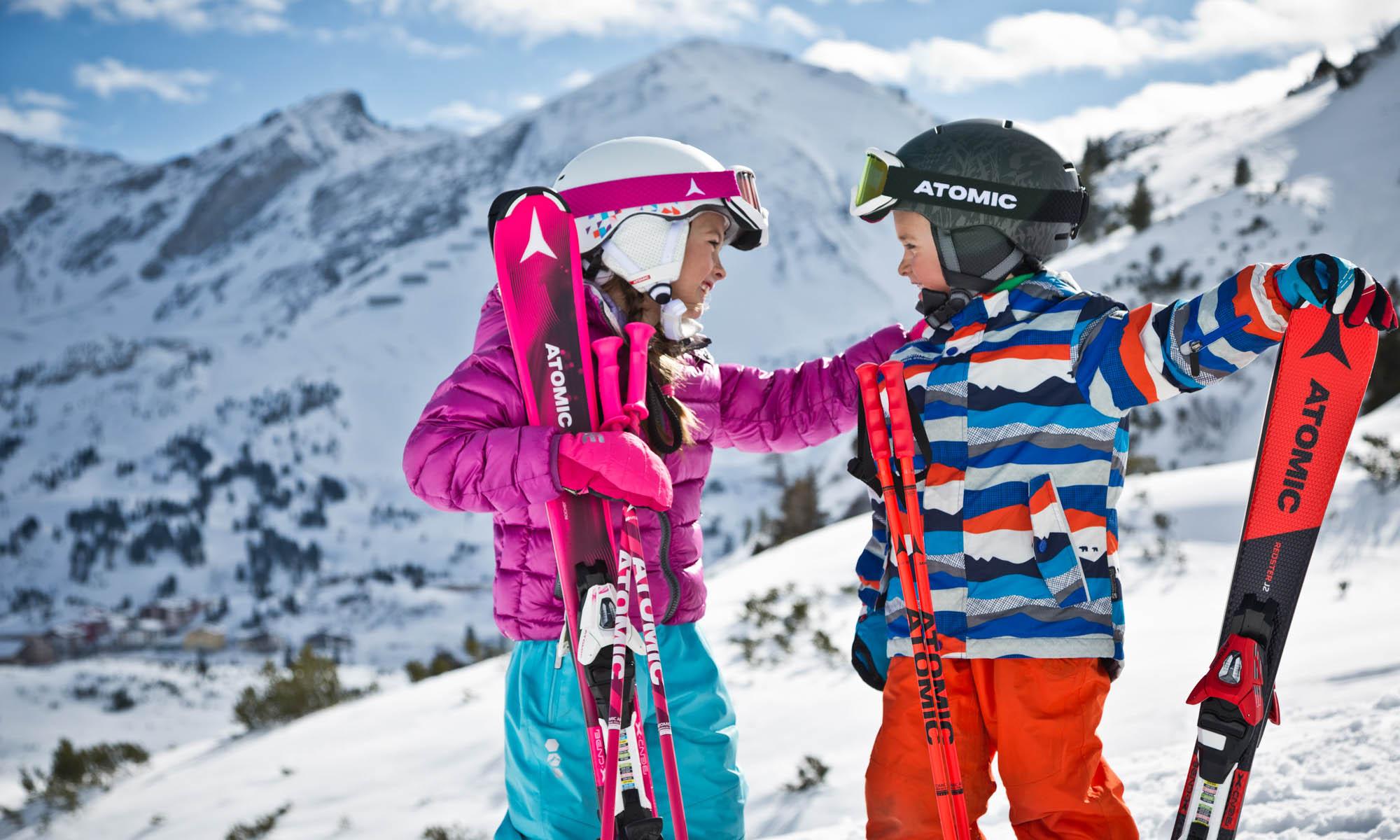 Een kleine jongen en meisje met ski´s en skistokken.