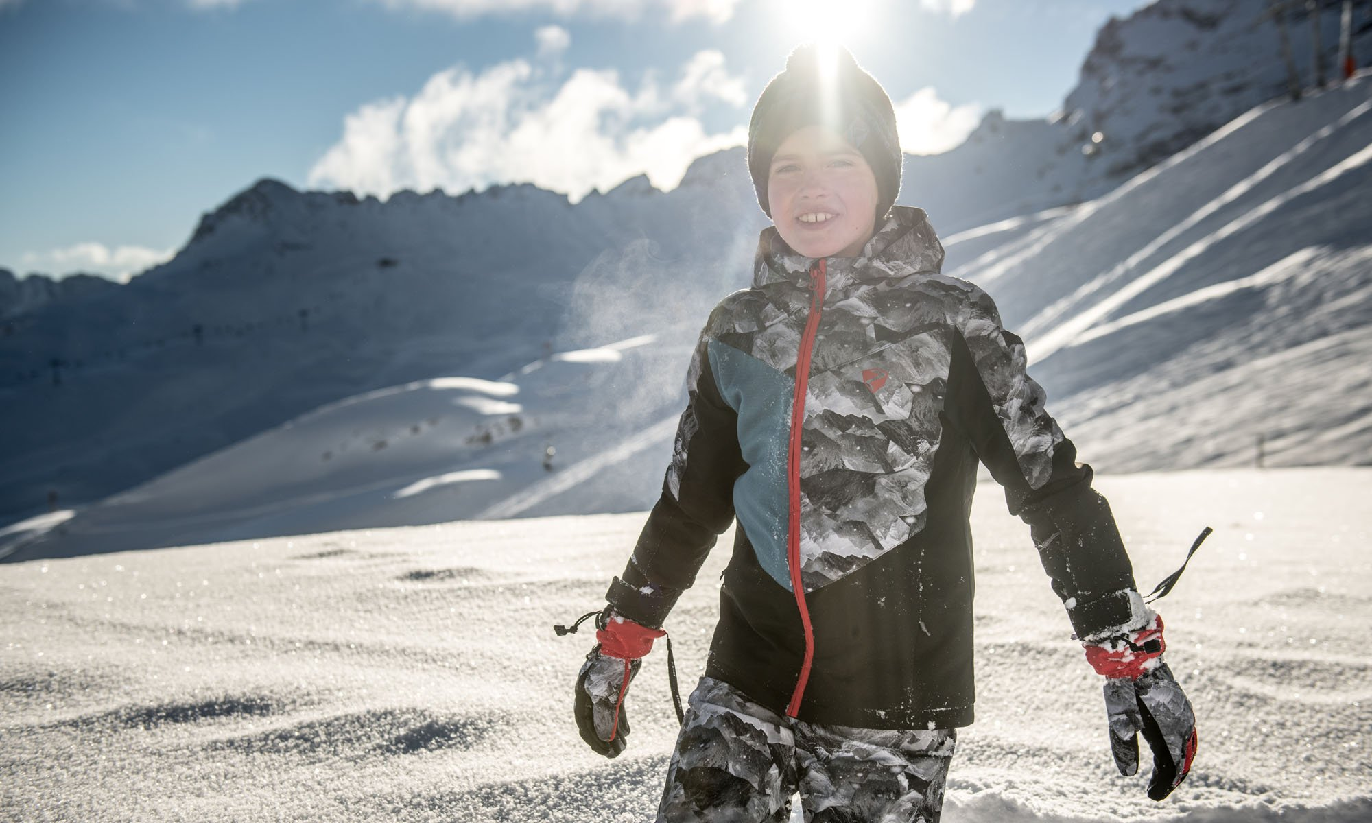 A young boy in a camouflage ski outfit.
