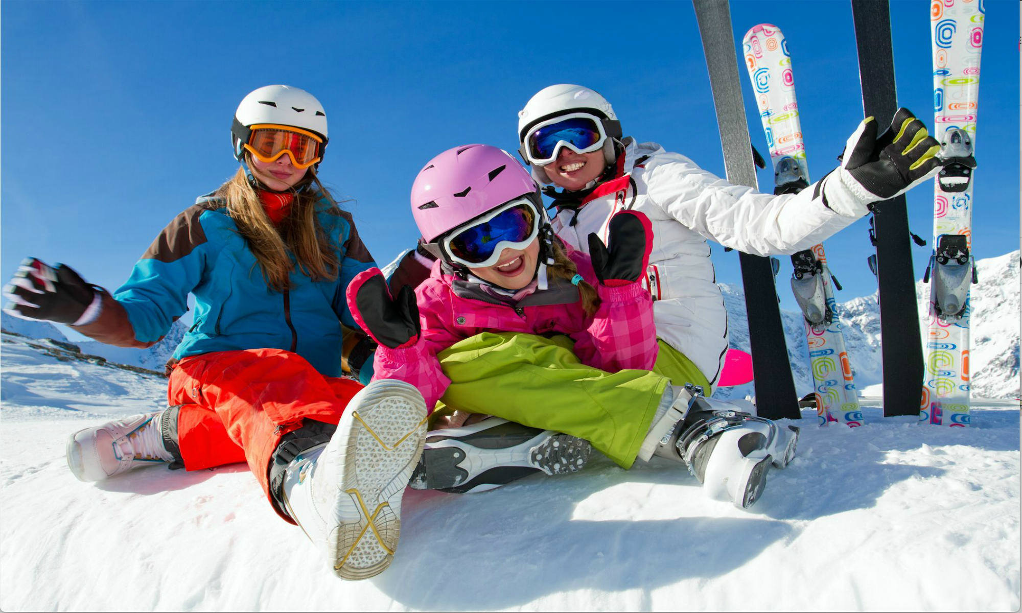 Family of happy skiers sitting on a snowy slope in Méribel.