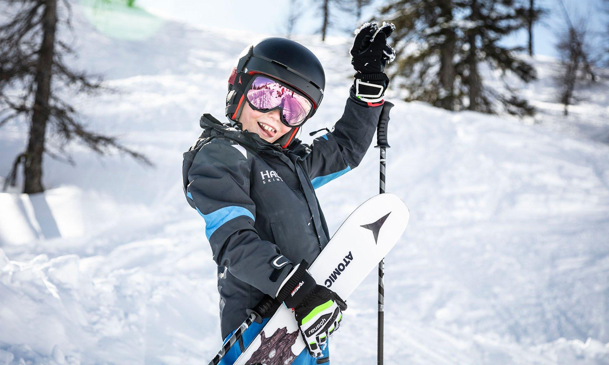 Ein Junge, der Ski und Skistöcke in der Hand hält.