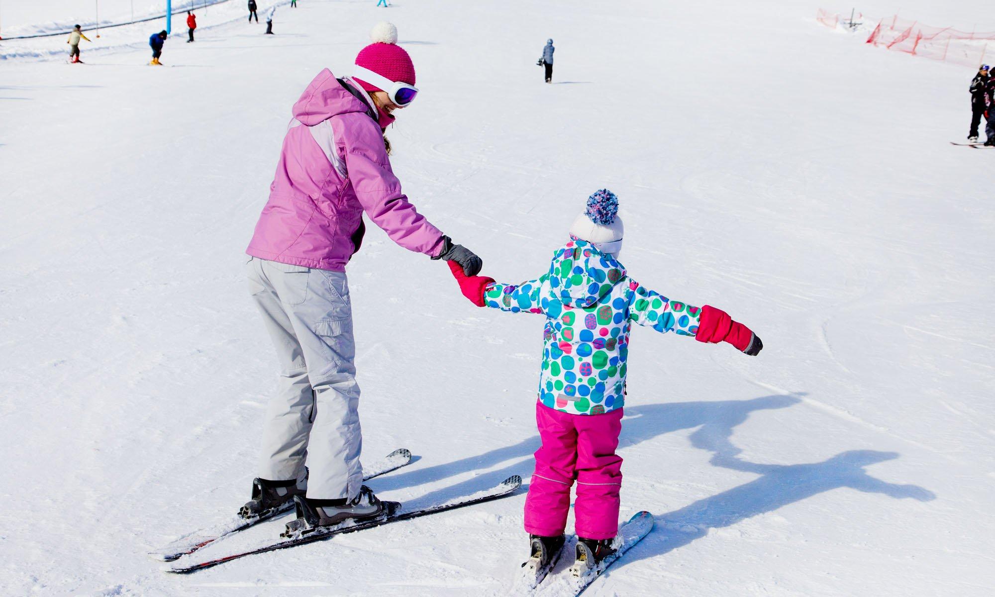Een kind en een privé-instructeur oefenen samen op de piste.