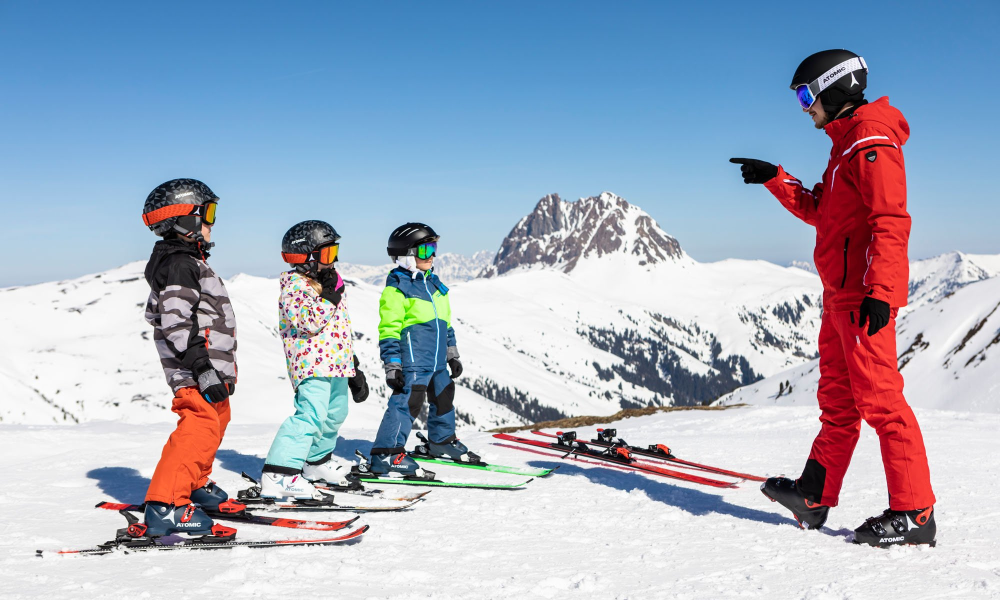 Drie kinderen krijgen instructies van een privé-instructeur op de piste.