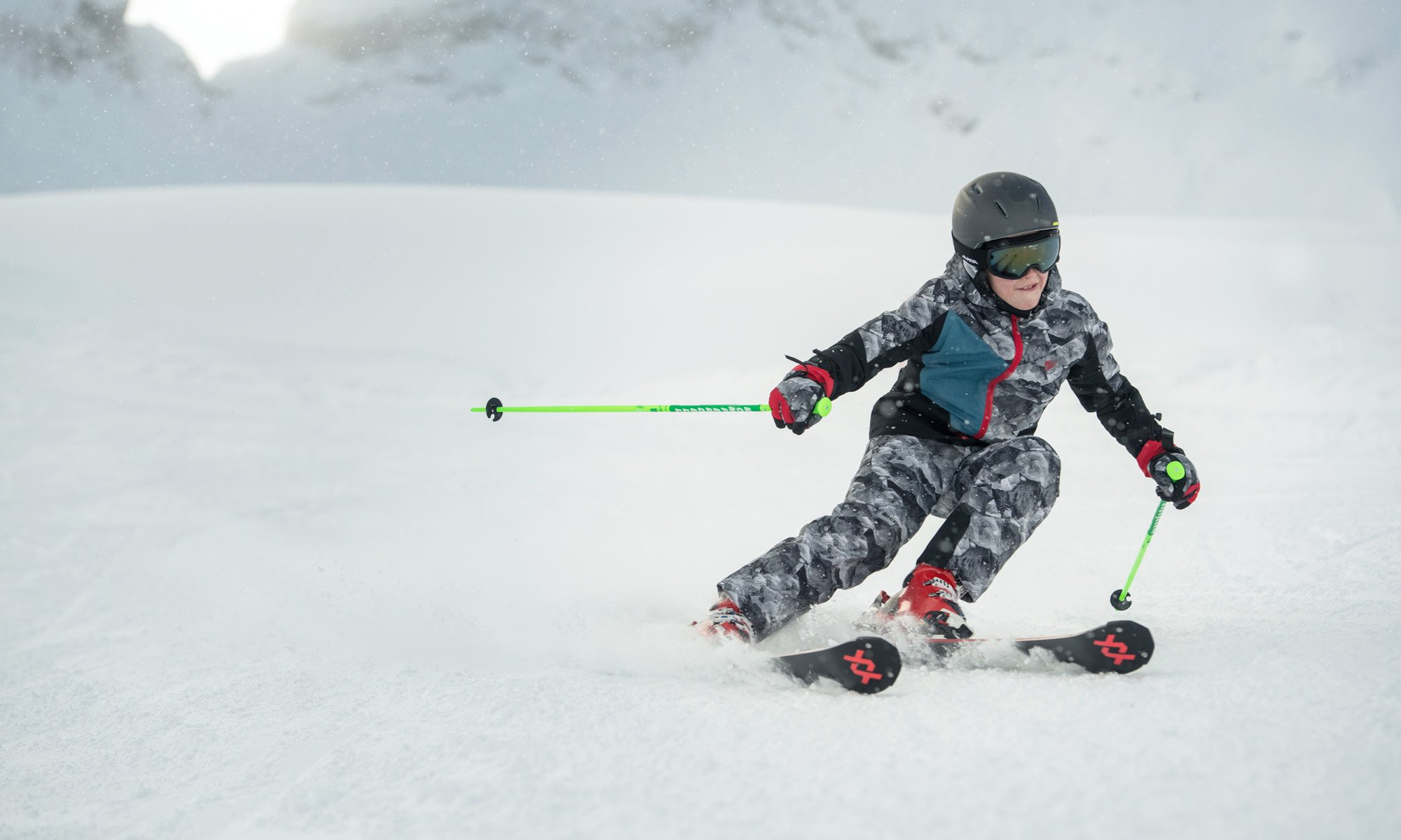 A boy skiing down the slopes in a grey camouflage outfit.