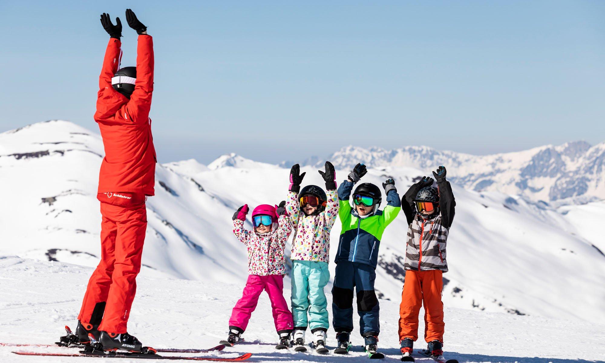 Een skileraar doet de wave met een groepje kinderen.