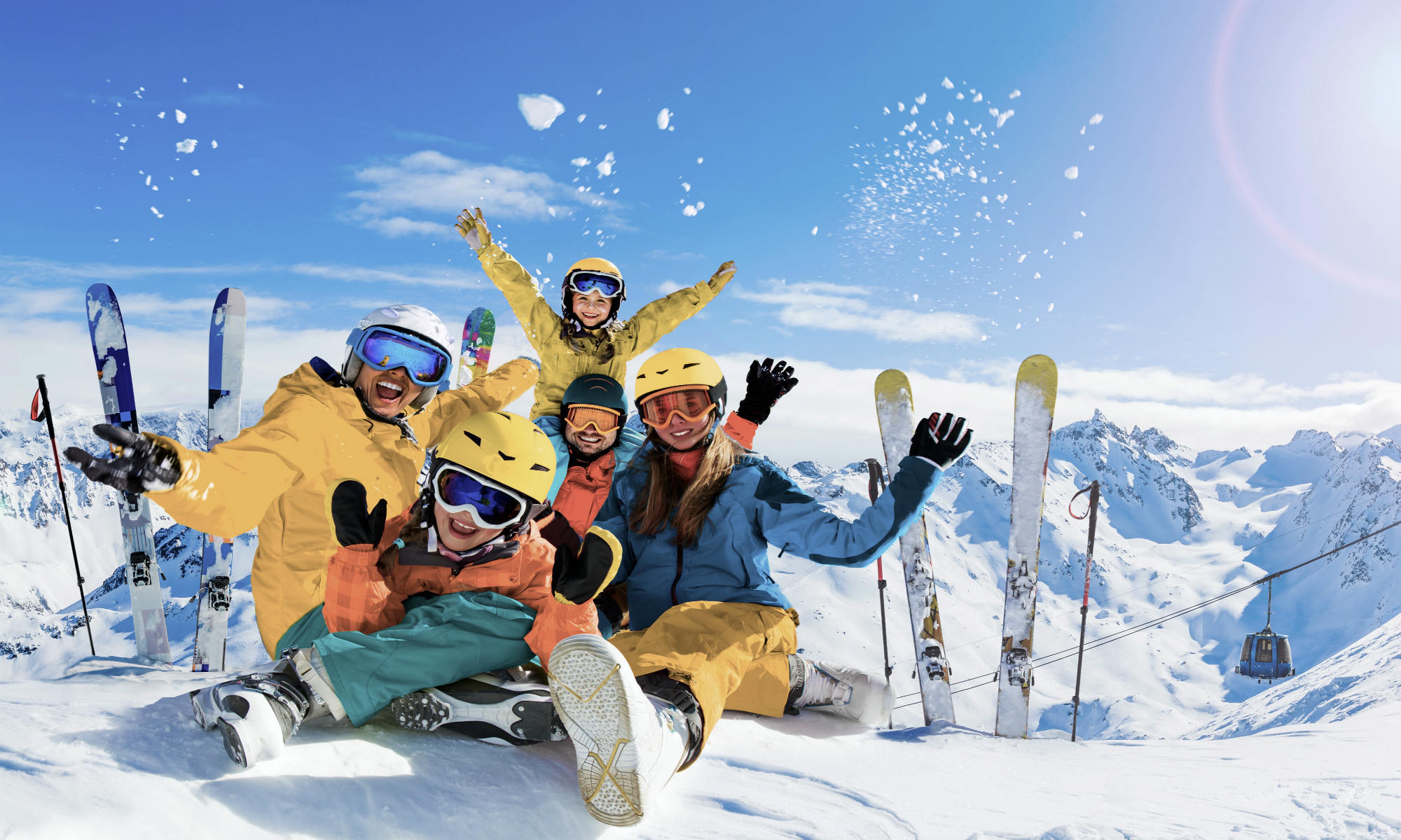 A family of skiers having fun at the top of a mountain.
