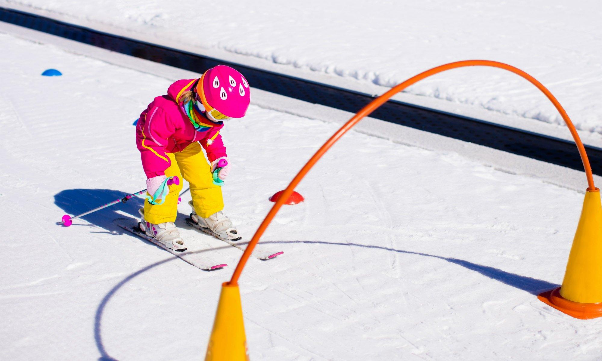 Una piccola sciatrice si appresta a sciare attraverso un ostacolo sulla neve a Bormio.