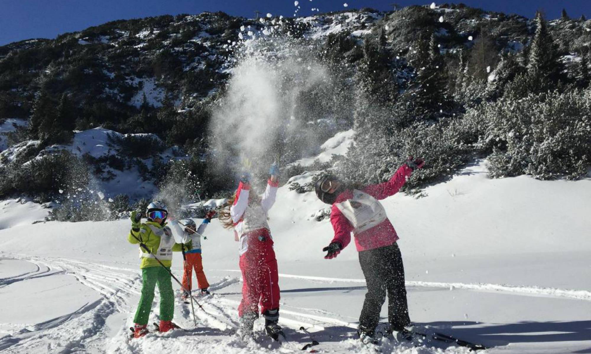 I partecipanti di un corso di sci ad Andalo lanciano la neve in aria.