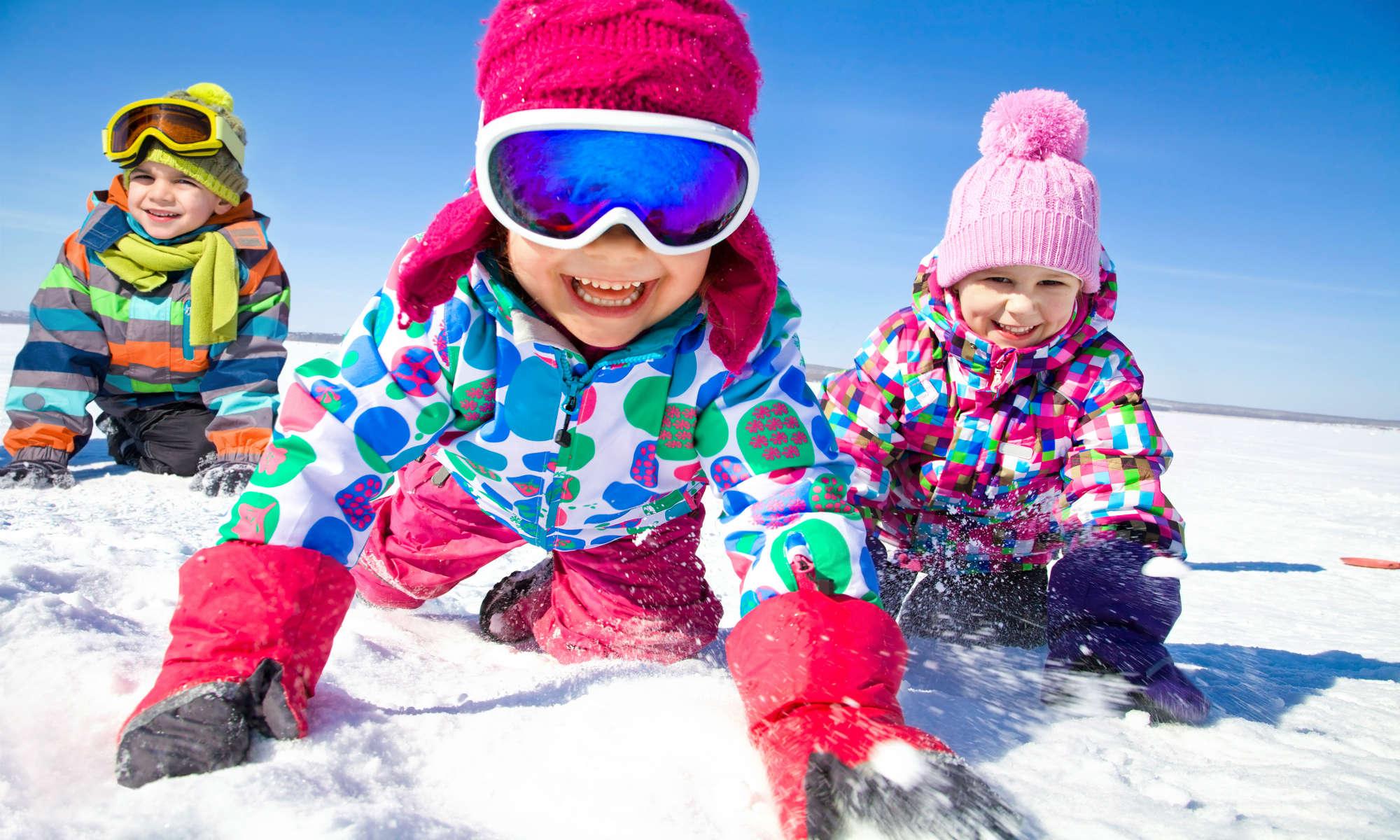 Tre bambini giocano con la neve a Bormio, mentre sorridono verso la macchina fotografica.