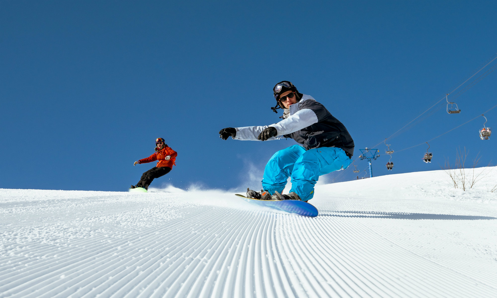 Two snowboarders boarding on freshly-groomed slopes