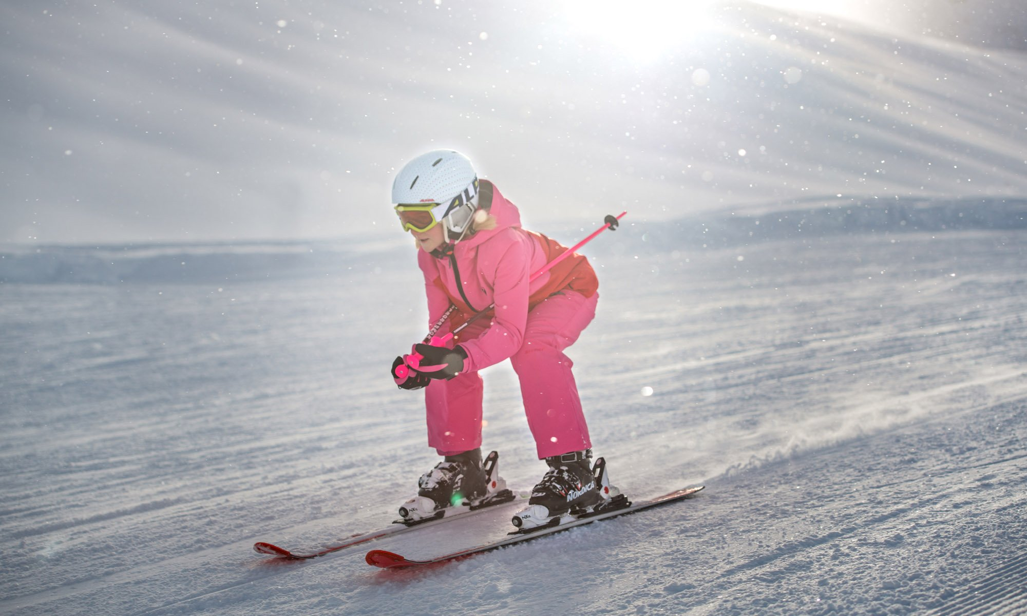 Une petite fille en tenue de ski rose.