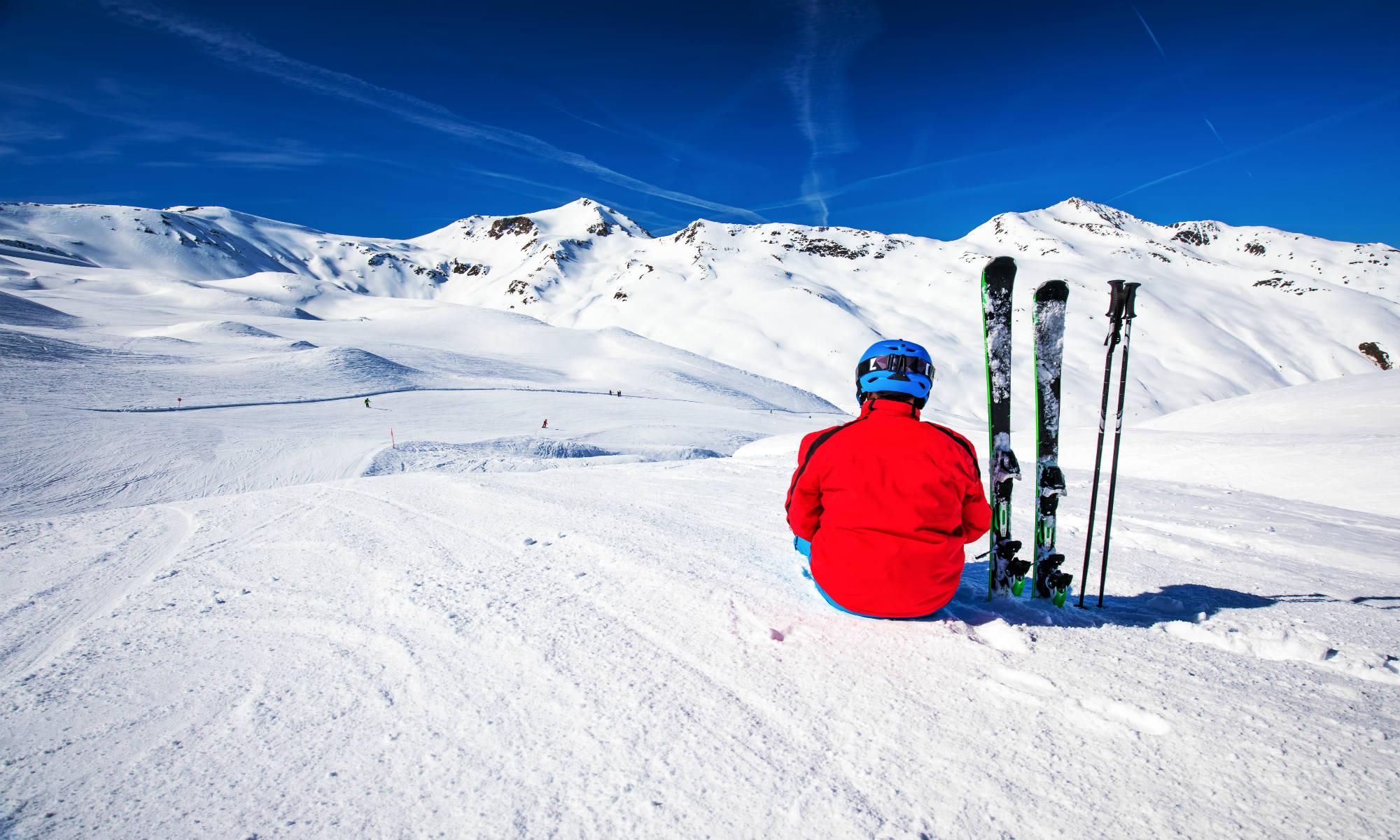 Uno sciatore si prende un momento di pausa, sedendosi sulla cima della montagna, ammirando le vette innevate circostanti.