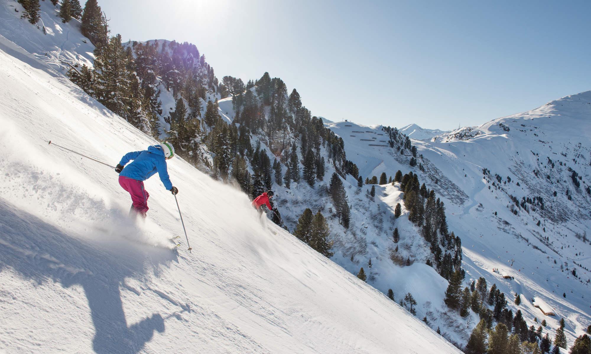 2 Skifahrer gleiten über die sonnige Harakiri-Abfahrt im schneesicheren Skigebiet Mayrhofen.