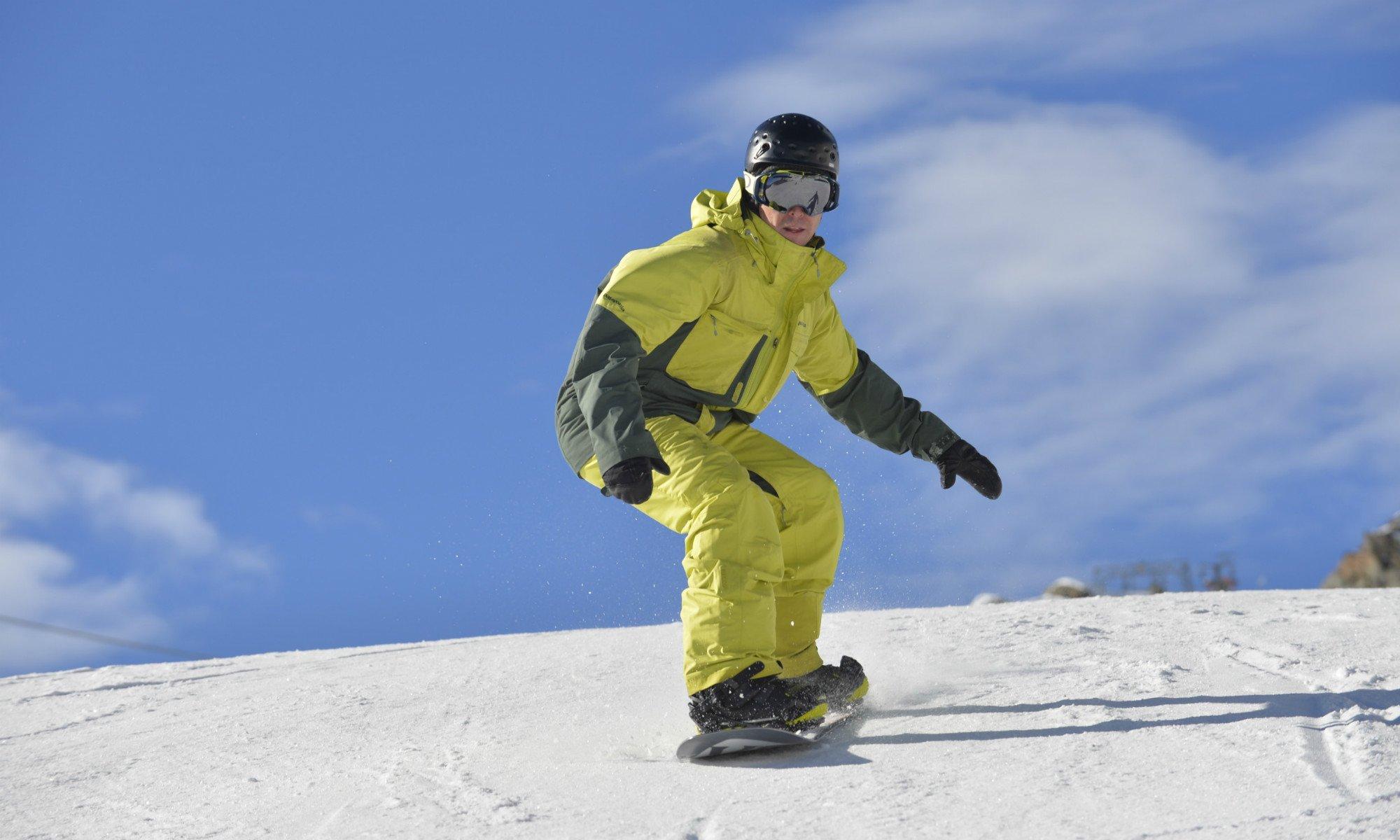 Ein Snowboarder auf einer schneebedeckten Skipiste am Stubaier Gletscher.