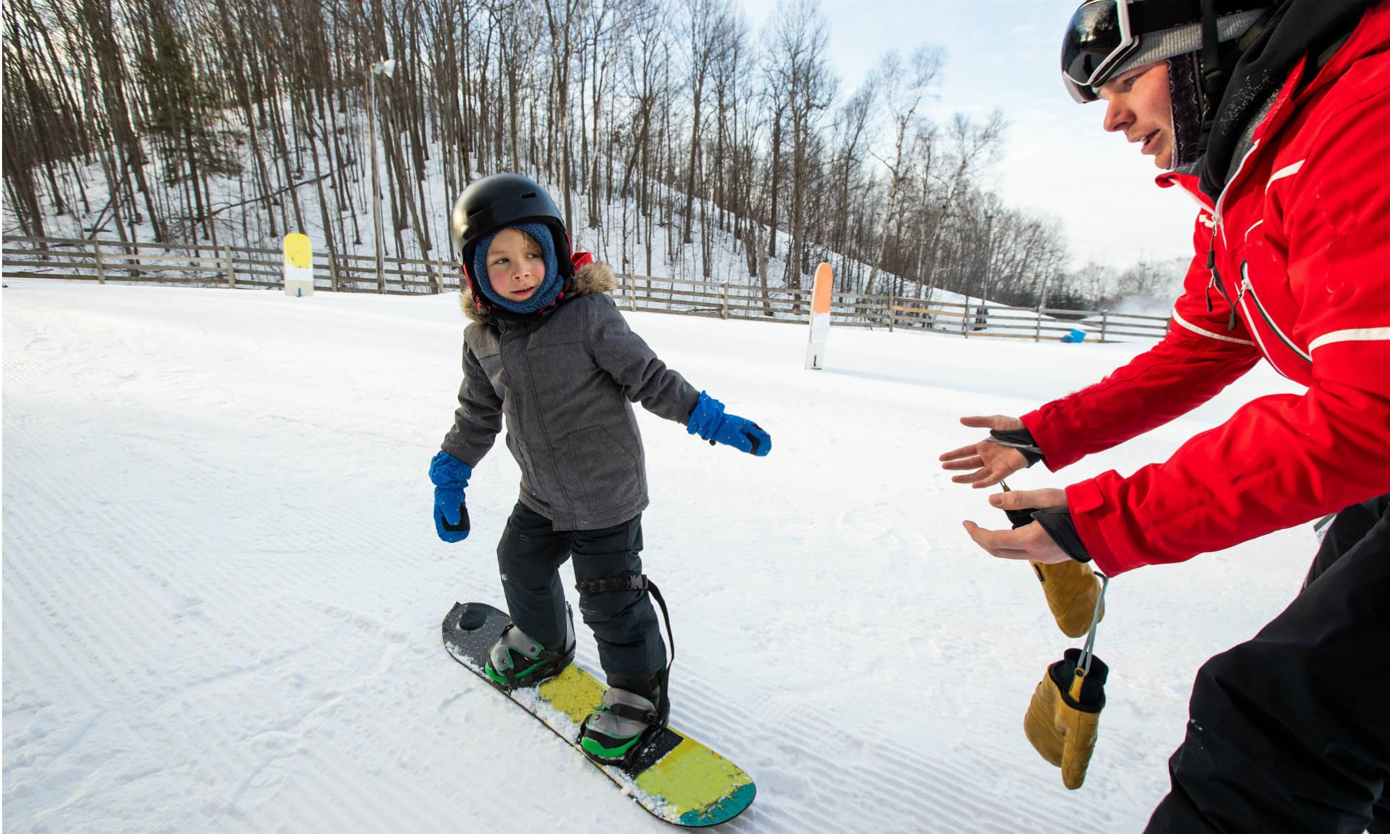 Ein kleiner Junge lernt das Snowboarden in einem Snowboardkurs in Österreich.