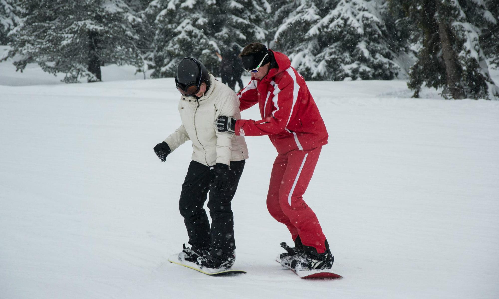 Eine Frau lernt das Snowboarden in einem privaten Snowboardkurs im Skigebiet Kreischberg in Österreich.