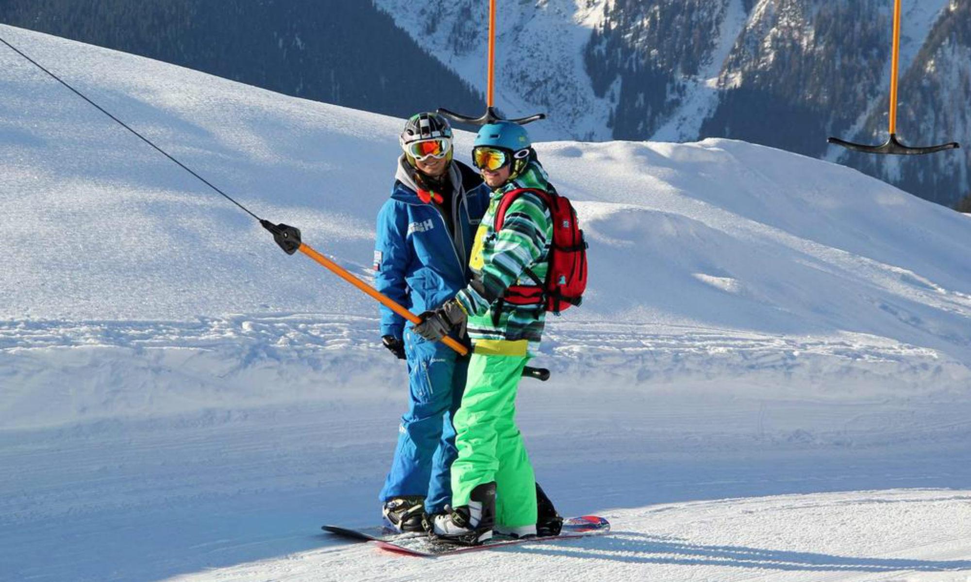 Ein Snowboardlehrer und ein Kursteilnehmer fahren mit einem Schlepplift im Skigebiet Mayrhofen.