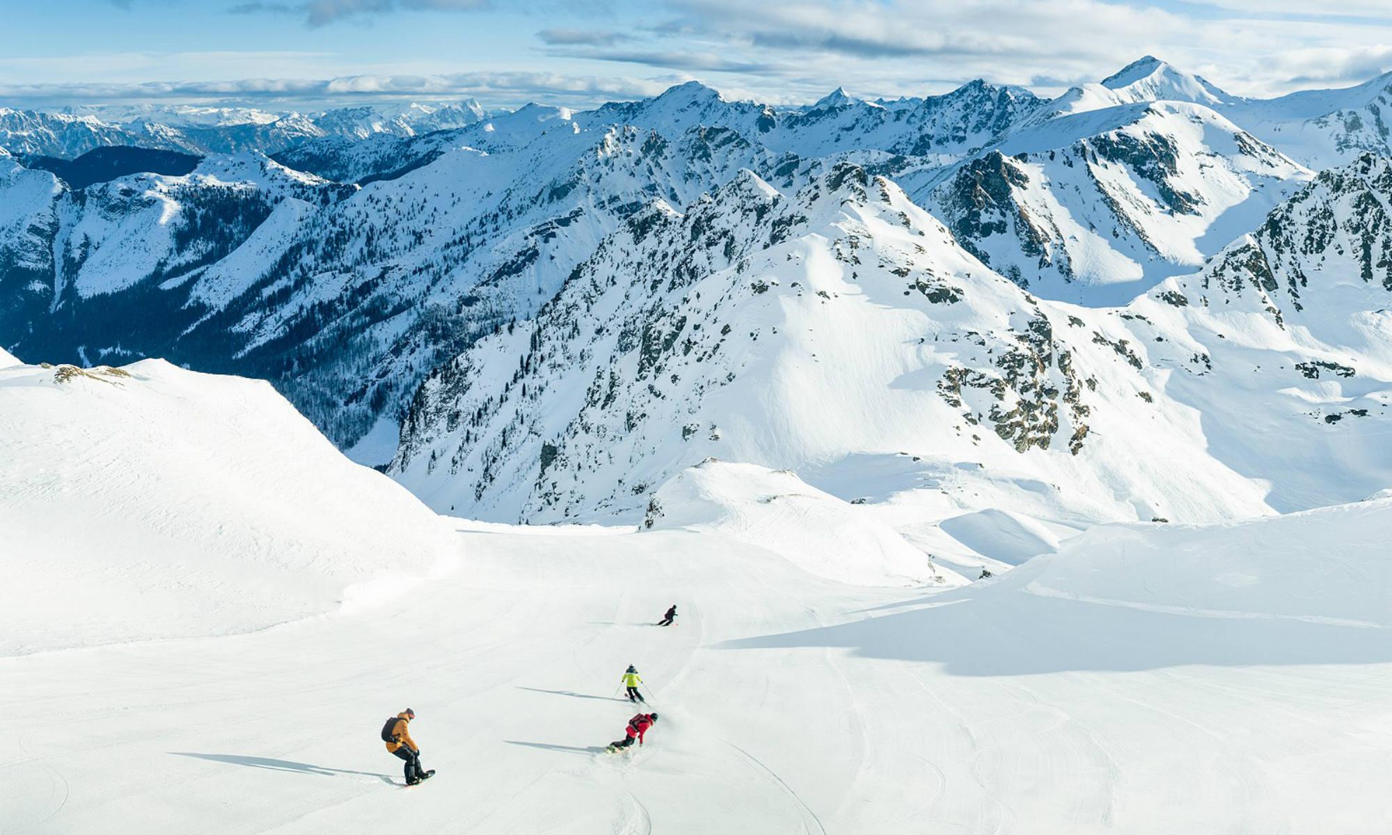 Eine Gruppe Snowboarder und Skifahrer auf einer verschneiten Piste im Skigebiet Obertauern.