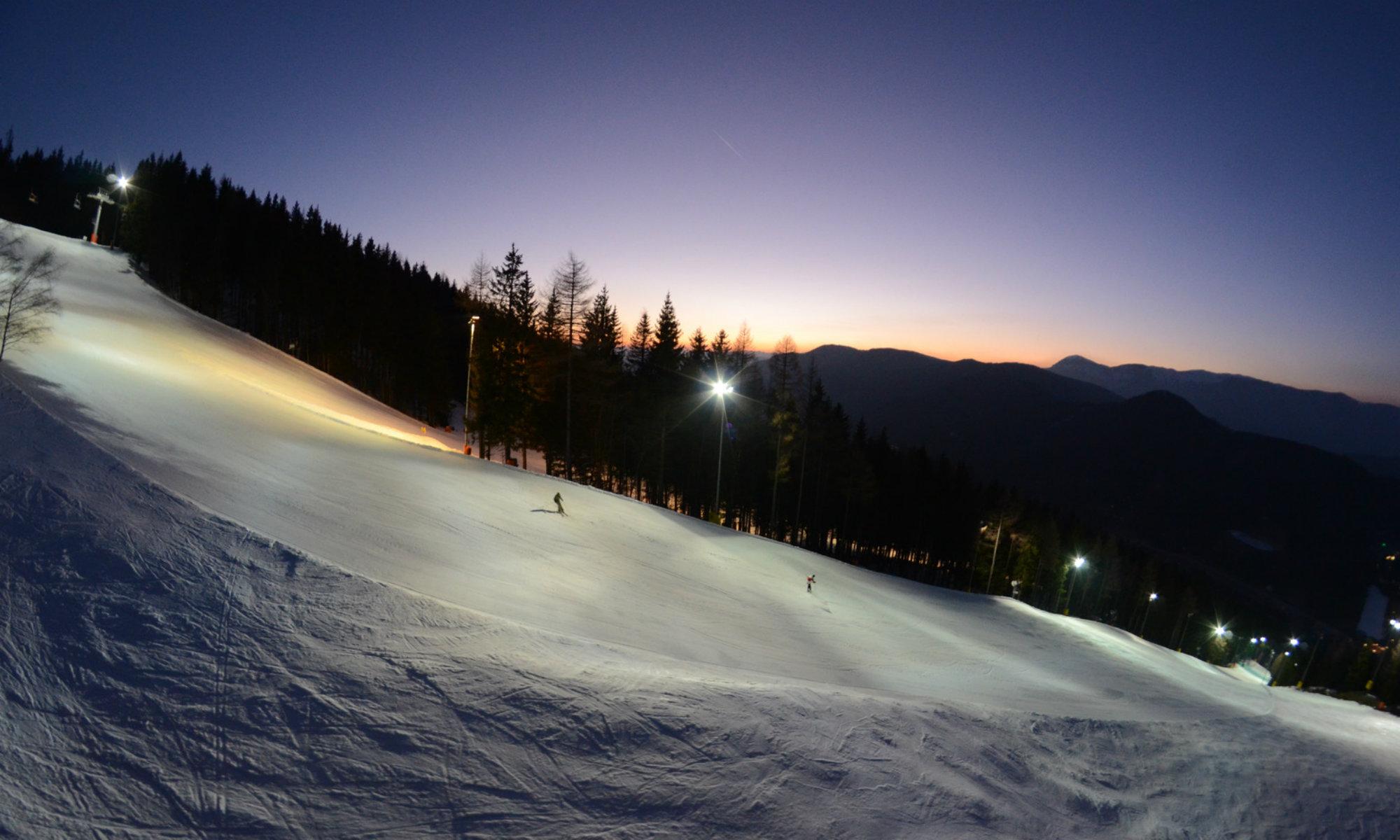 Zwei Wintersportler auf einer beleuchteten Piste beim Nachtsnowboarden am Zauberberg in Österreich.
