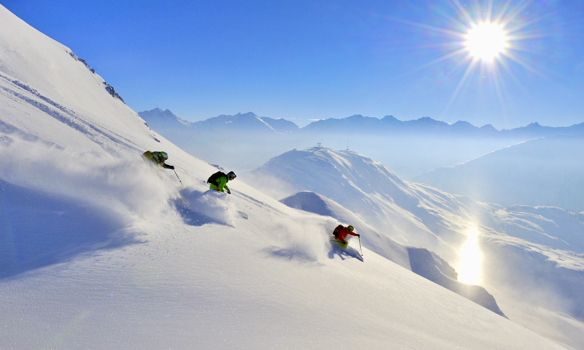 Three freestylers skiing on powder snow in St. Anton