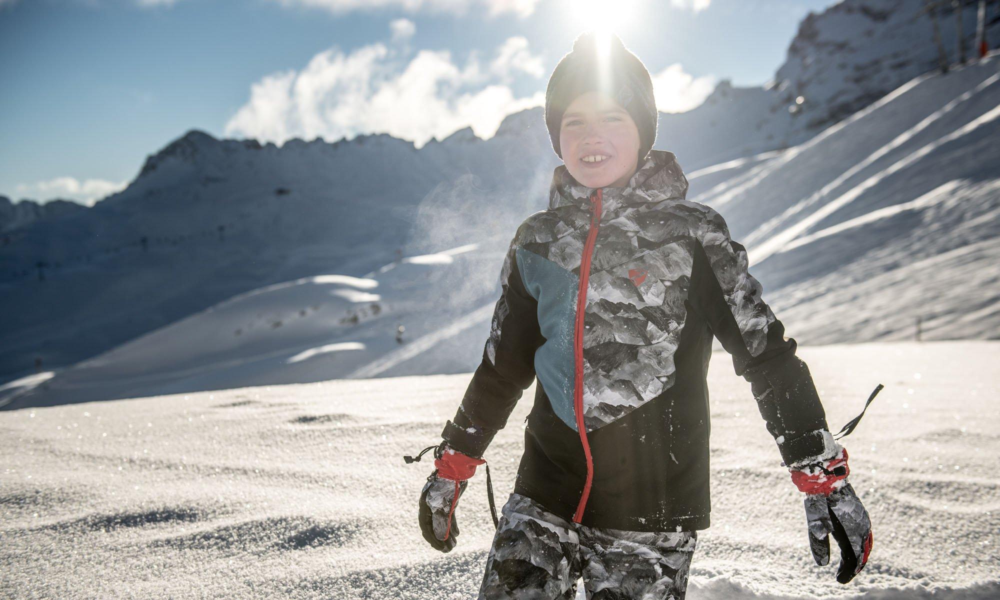 Ein Junge im grauen Ski Outfit.