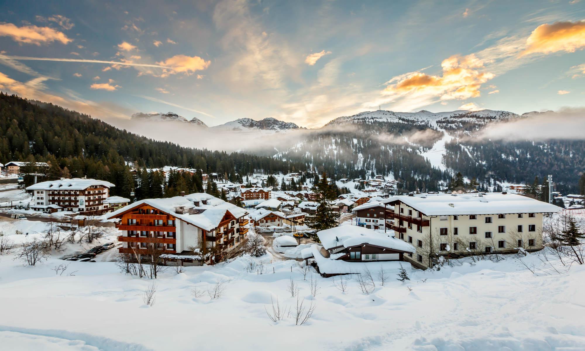 Il sole sorge dietro le Dolomiti, illuminando il paese di Madonna di Campiglio.