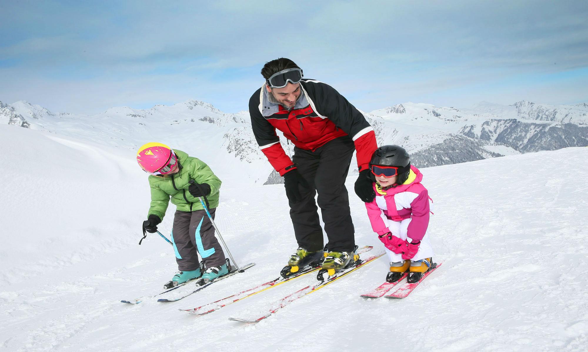 Un maestro di sci insegna a due bambini piccoli come effettuare le loro prime discese sulla neve.