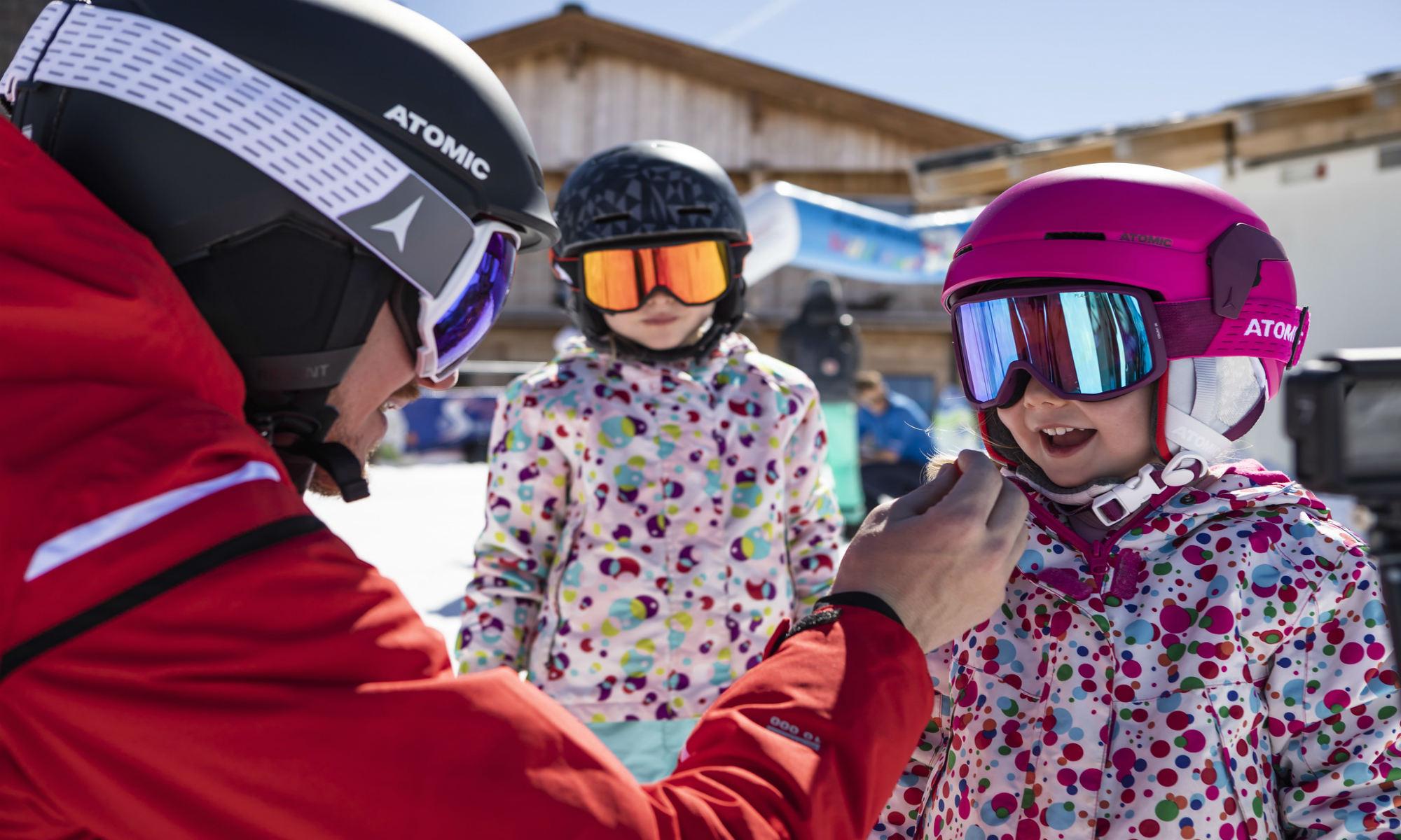Een skileraar is bezig aan de voorbereidingen op de skiles met een van zijn leerlingen.