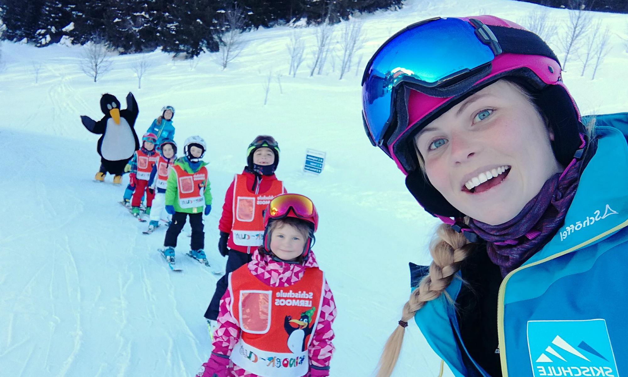 Een skilerares poseert voor een foto met haar leerlingen en BOBO de pinguïn.