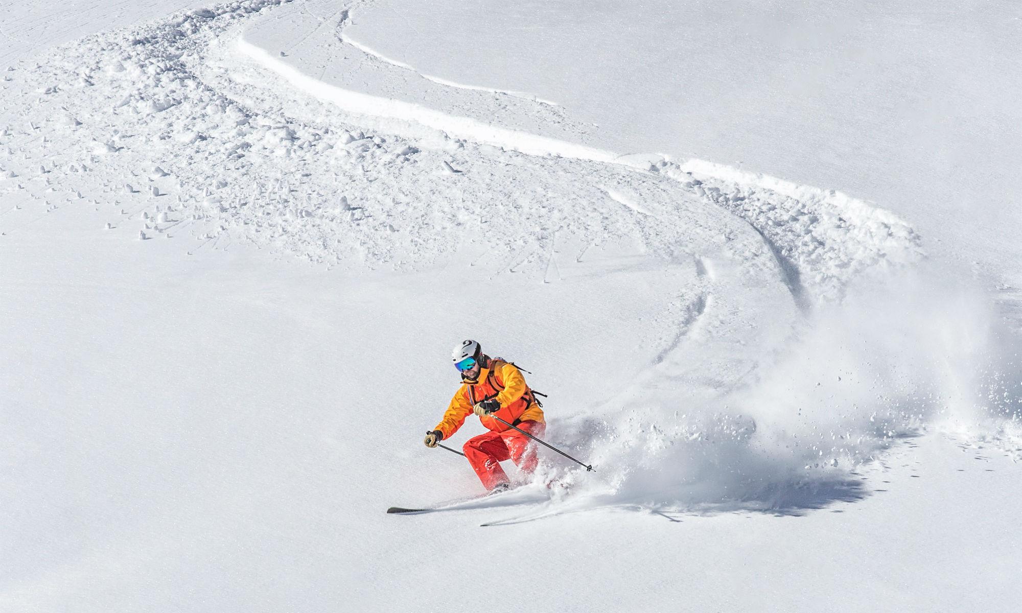 Un skieur fait jaillir la poudreuse sous ses skis lors d'une session de freeride.