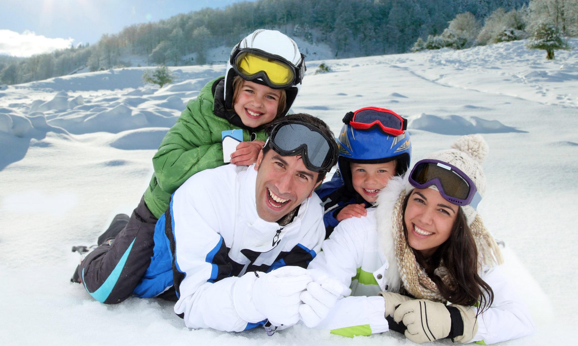 Une famille souriante pose allongée dans la neige.