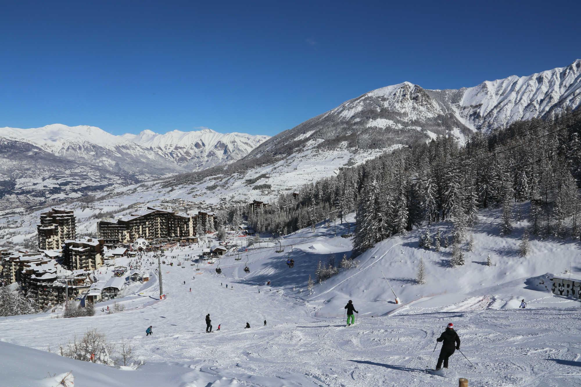 Des skieurs descendent une piste de ski en direction du village Les Orres 1650 sous un grand ciel bleu.
