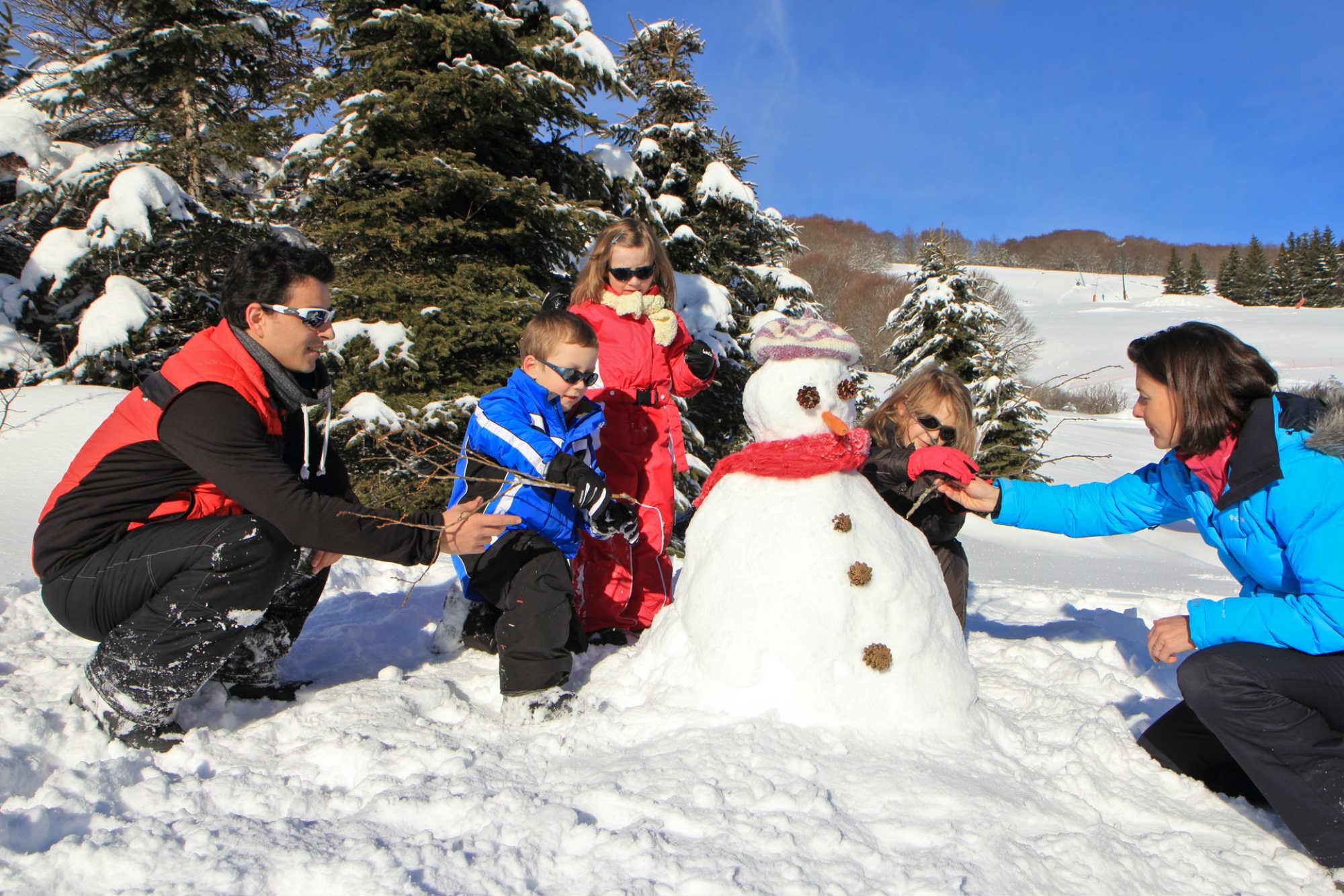 Une famille construit un bonhomme de neige à Super Besse.